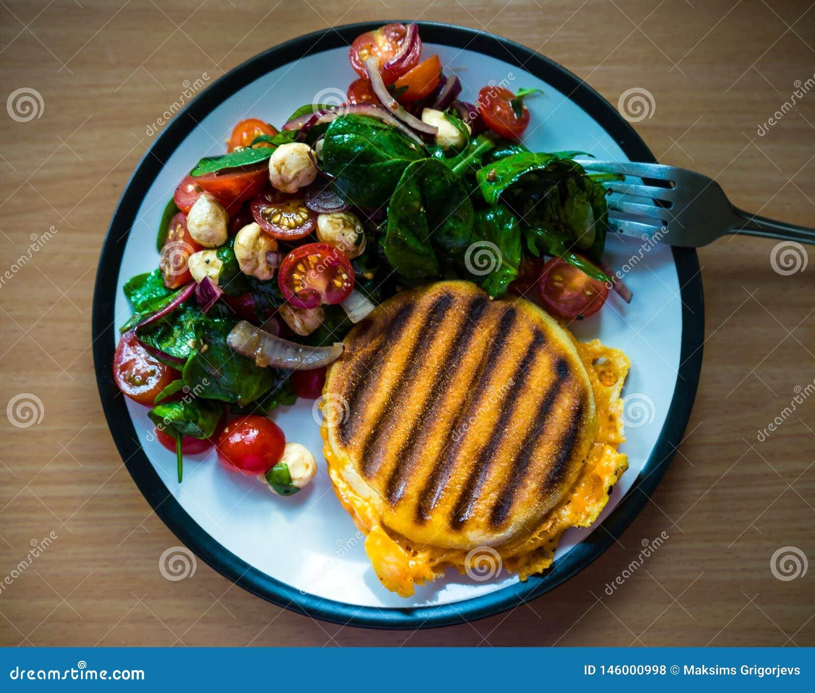 El desayuno hecho en casa asó a la parrilla el bocadillo inglés del miffin sirvió con la ensalada lateral: tomates de cereza, moz