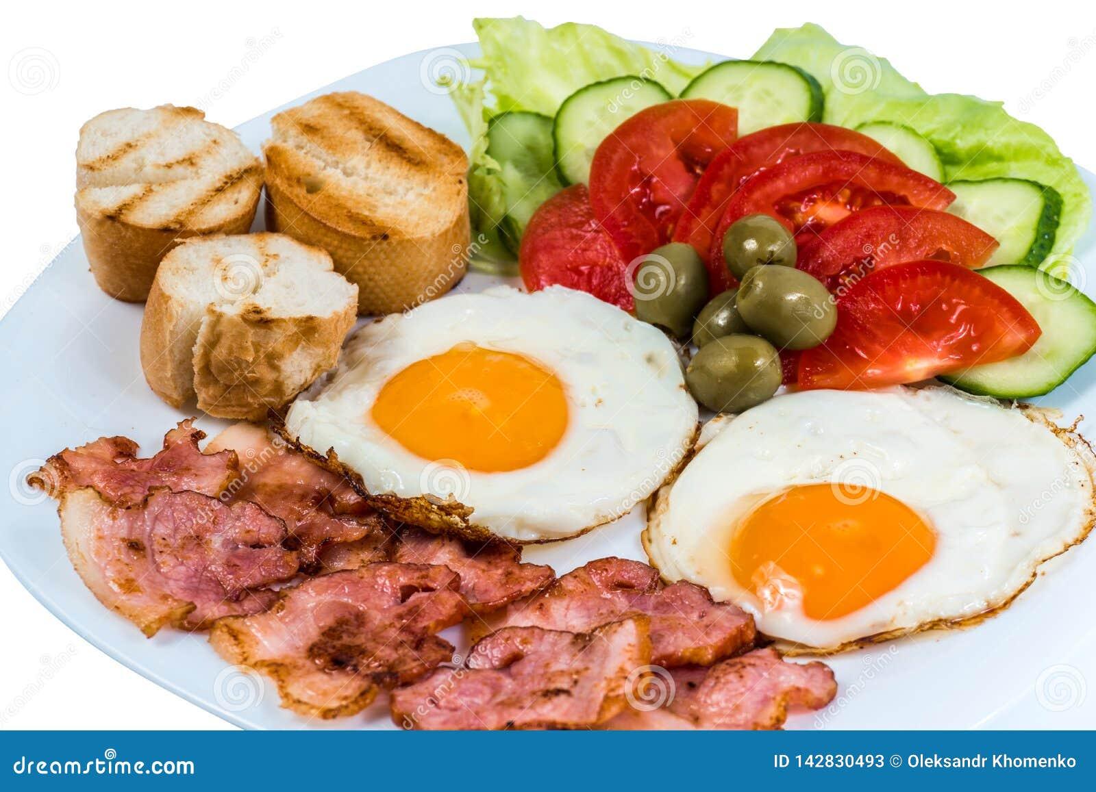 El desayuno el huevo frito que las verduras frescas frieron el tocino y aceitunas en una placa blanca