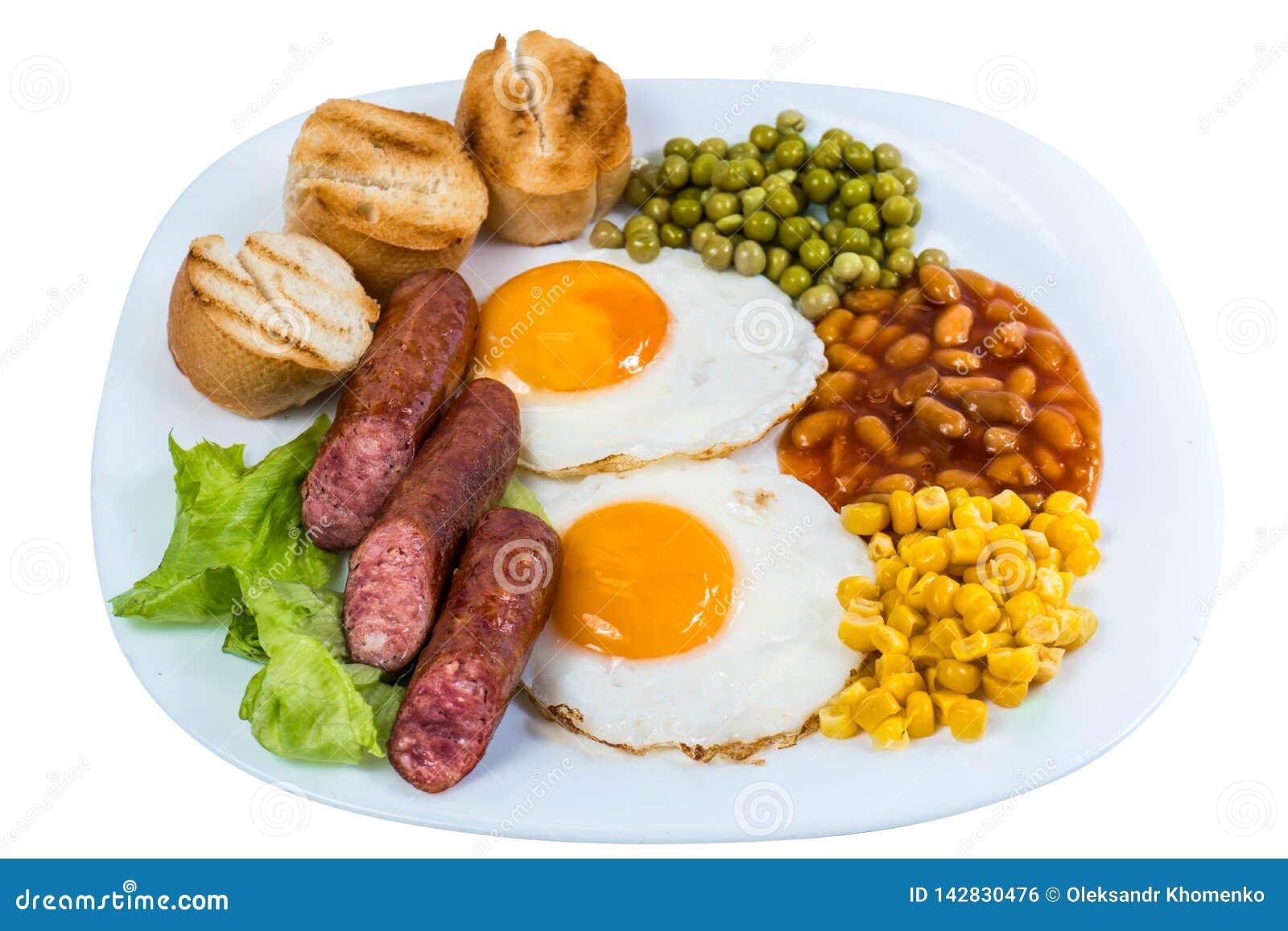 El desayuno los guisantes del huevo frito, los granos del maíz, las habas y las salchichas fritas en una placa blanca