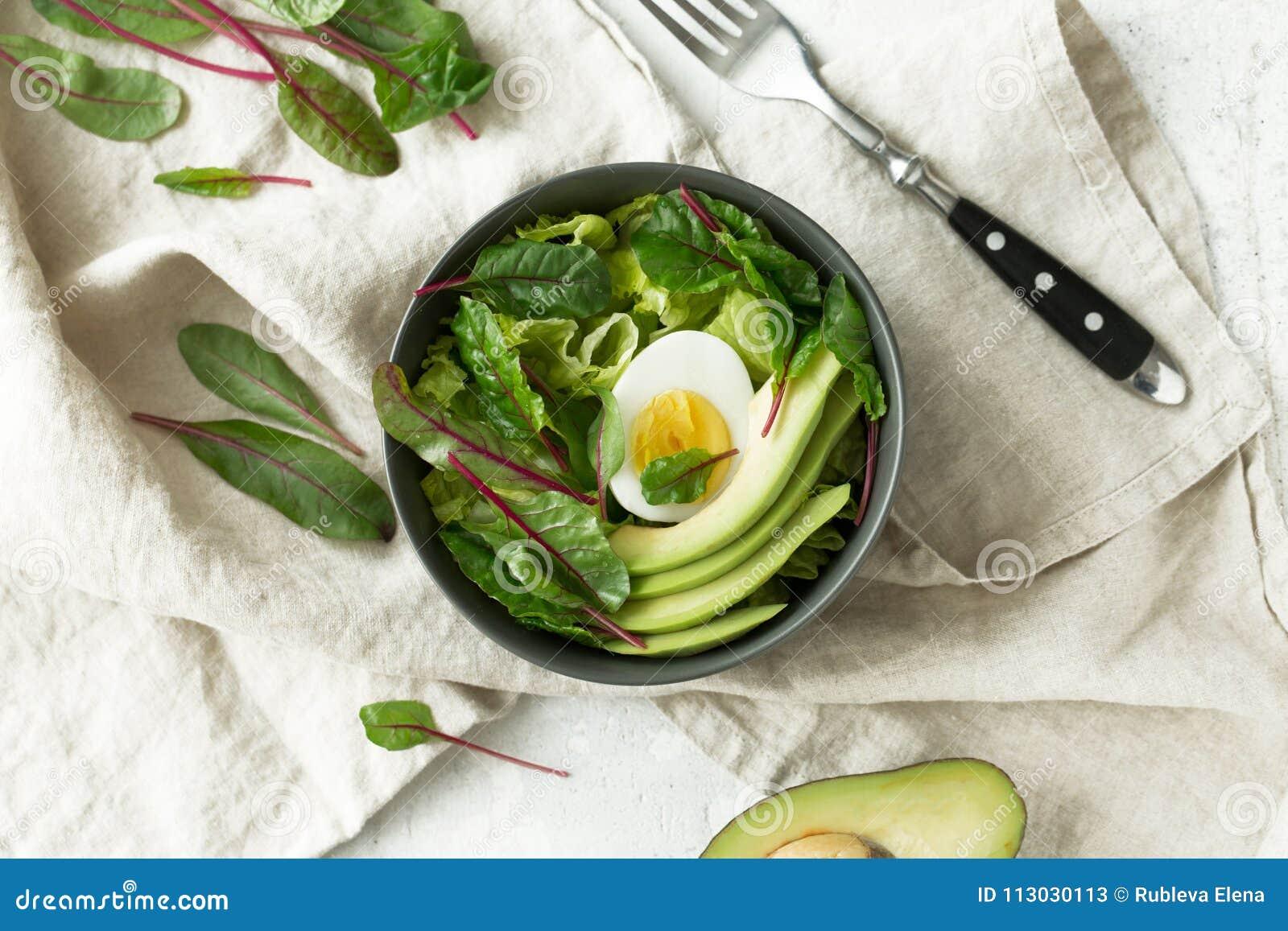 El desayuno vegetariano sano rueda con la ensalada, el aguacate y el huevo, visión superior Consumición limpia, concepto de la co