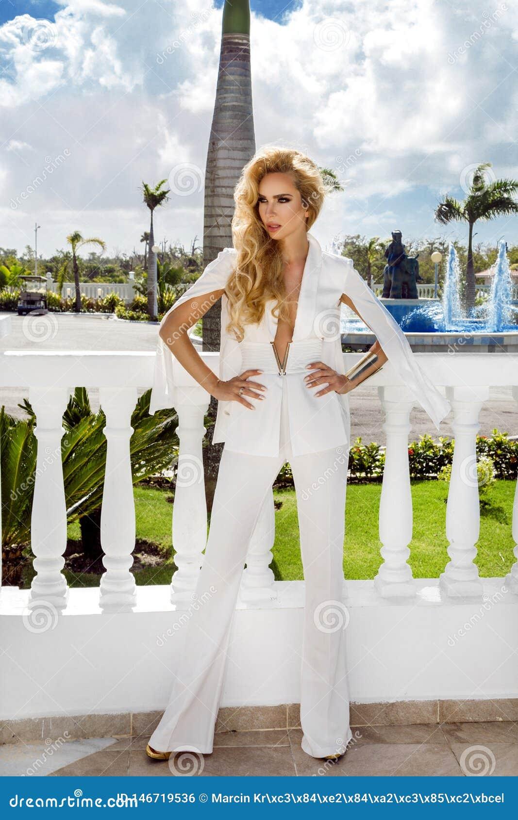 El desgaste rubio joven de la mujer acertada atractiva hermosa en mono blanco elegante y los tacones altos agarran la ropa acceso