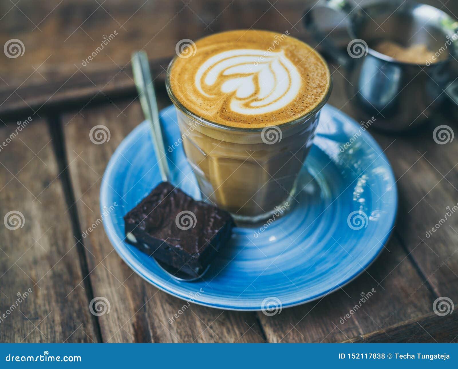 El desmoche de flautín del café del Latte con arte de la flor de la leche en pequeño vidrio con un pedazo de brownie hechos en ca