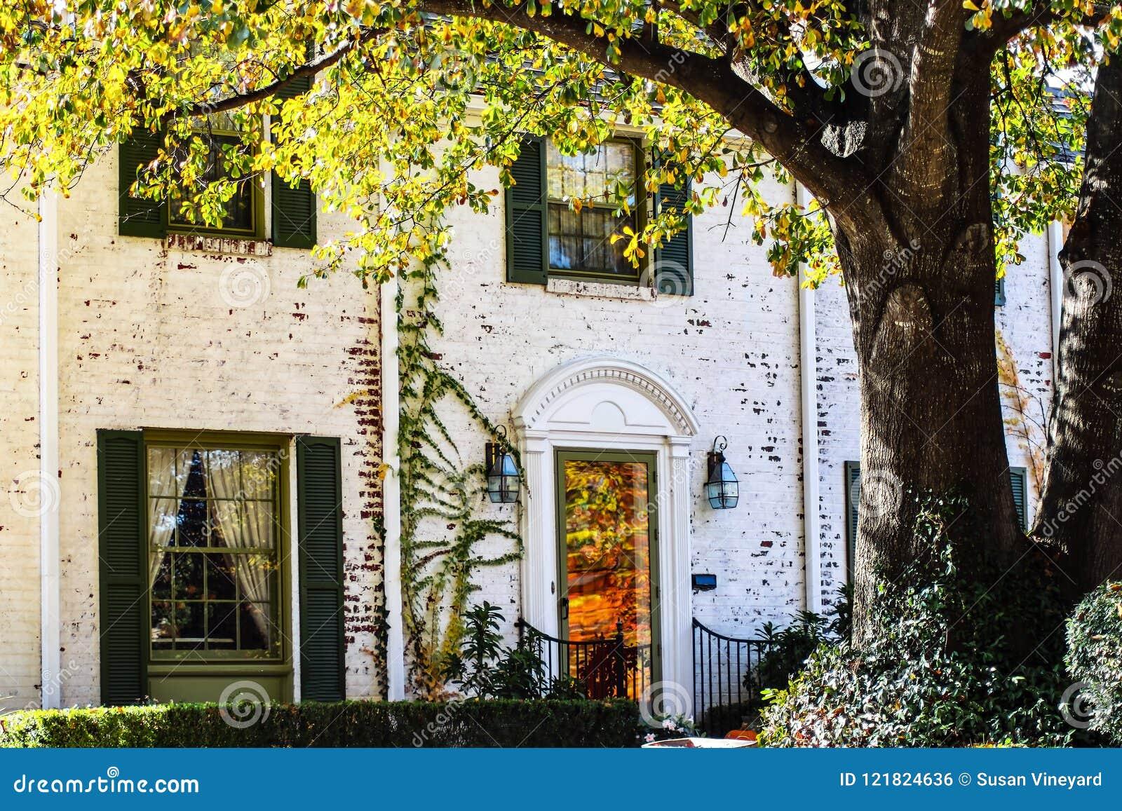 El detalle de la casa pintada blanco exclusivo de dos pisos del ladrillo con reflexiones de la caída se va en la puerta principal