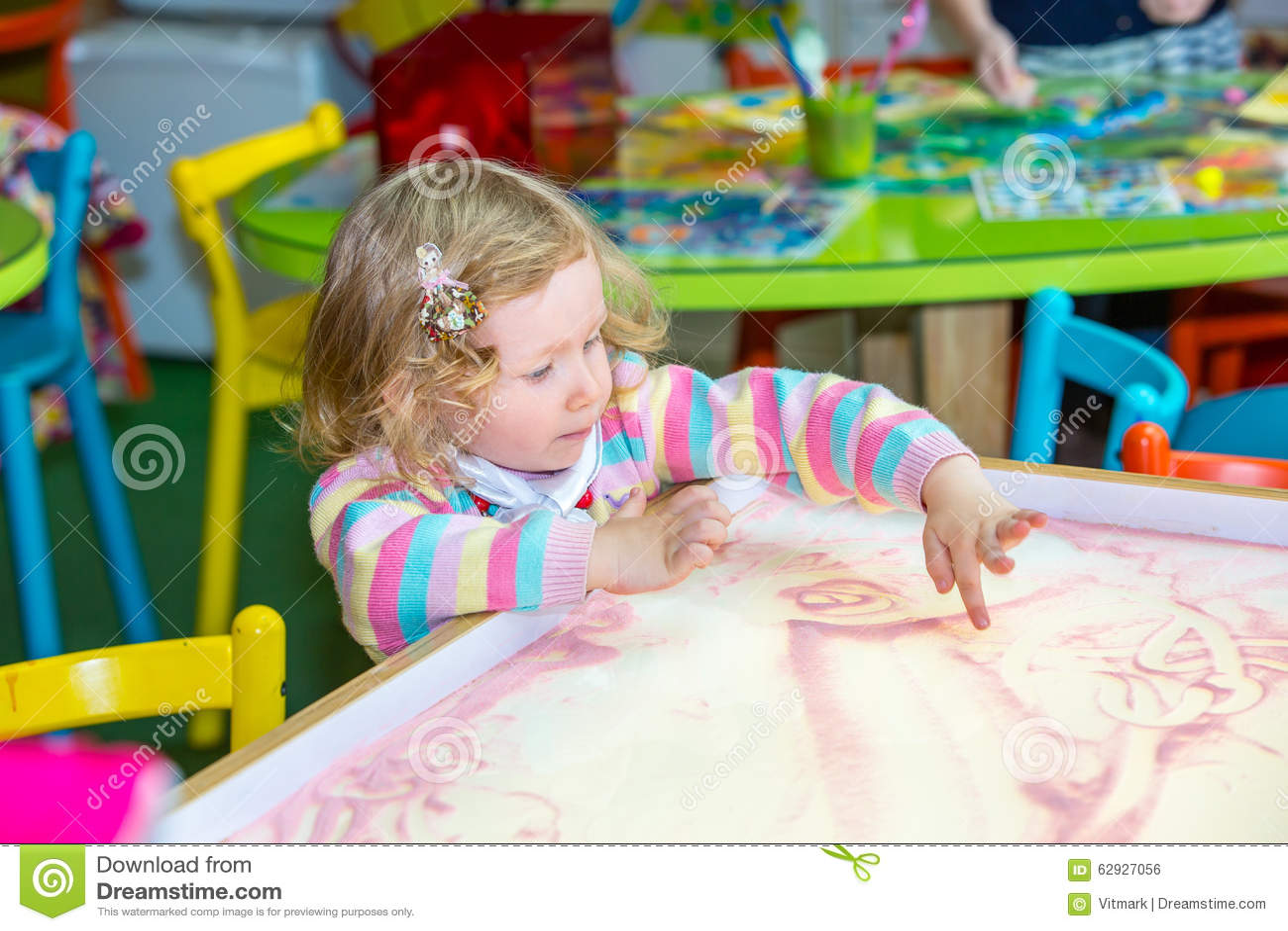 El dibujo lindo de la muchacha del niño dibuja la arena que se convierte en preescolar en la tabla en guardería