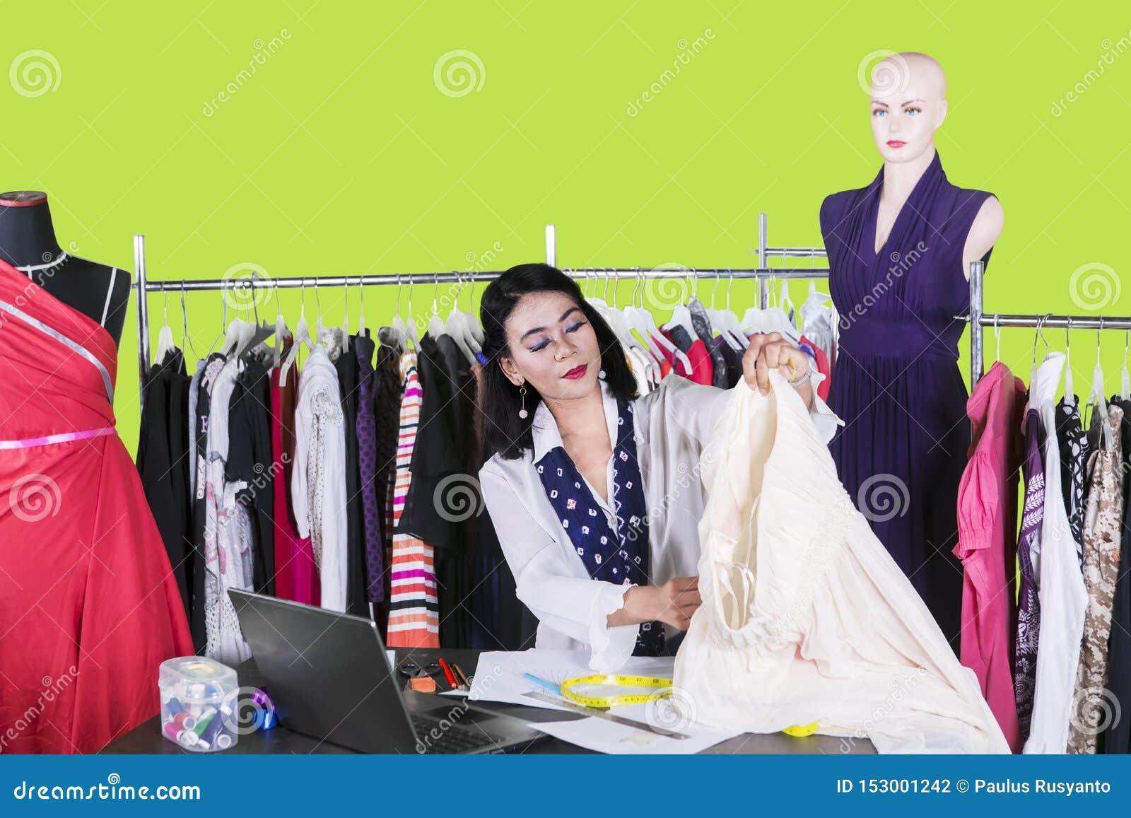 El diseñador de moda joven sostiene una tela en estudio