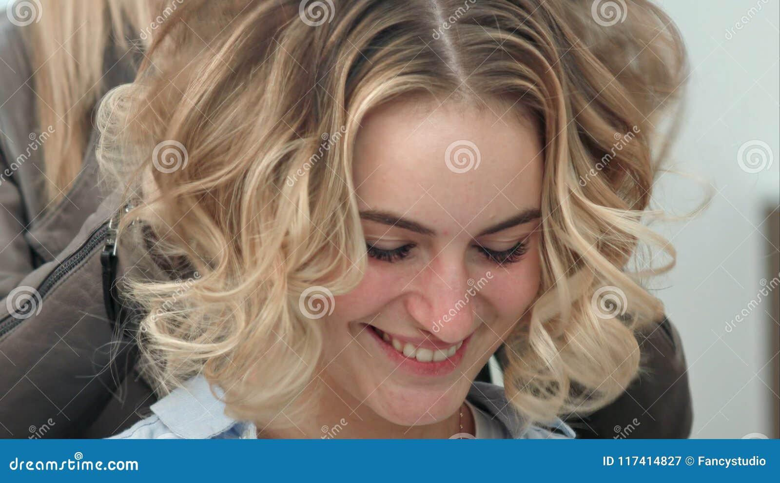 El diseñar final del pelo rizado del modelo del peluquero en salón de belleza