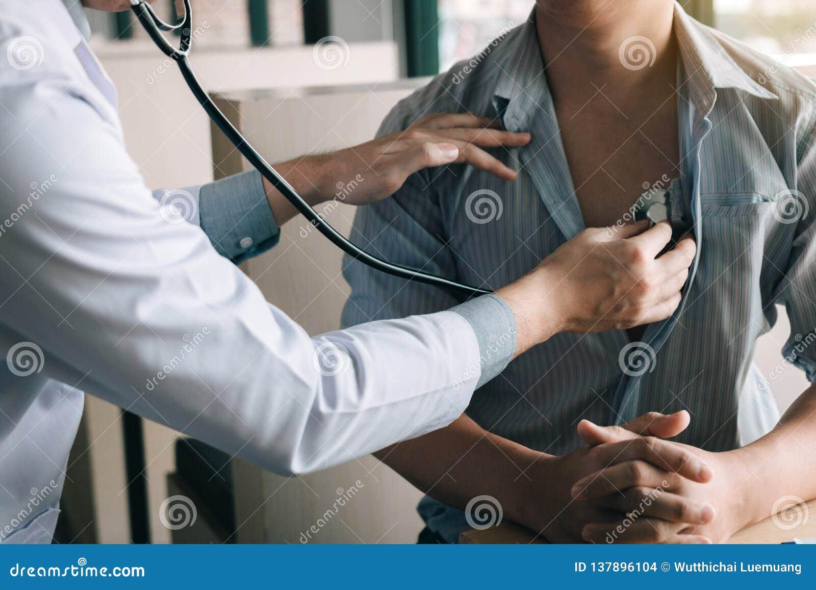 El doctor asiático está utilizando un estetoscopio para escuchar el latido del corazón del paciente mayor