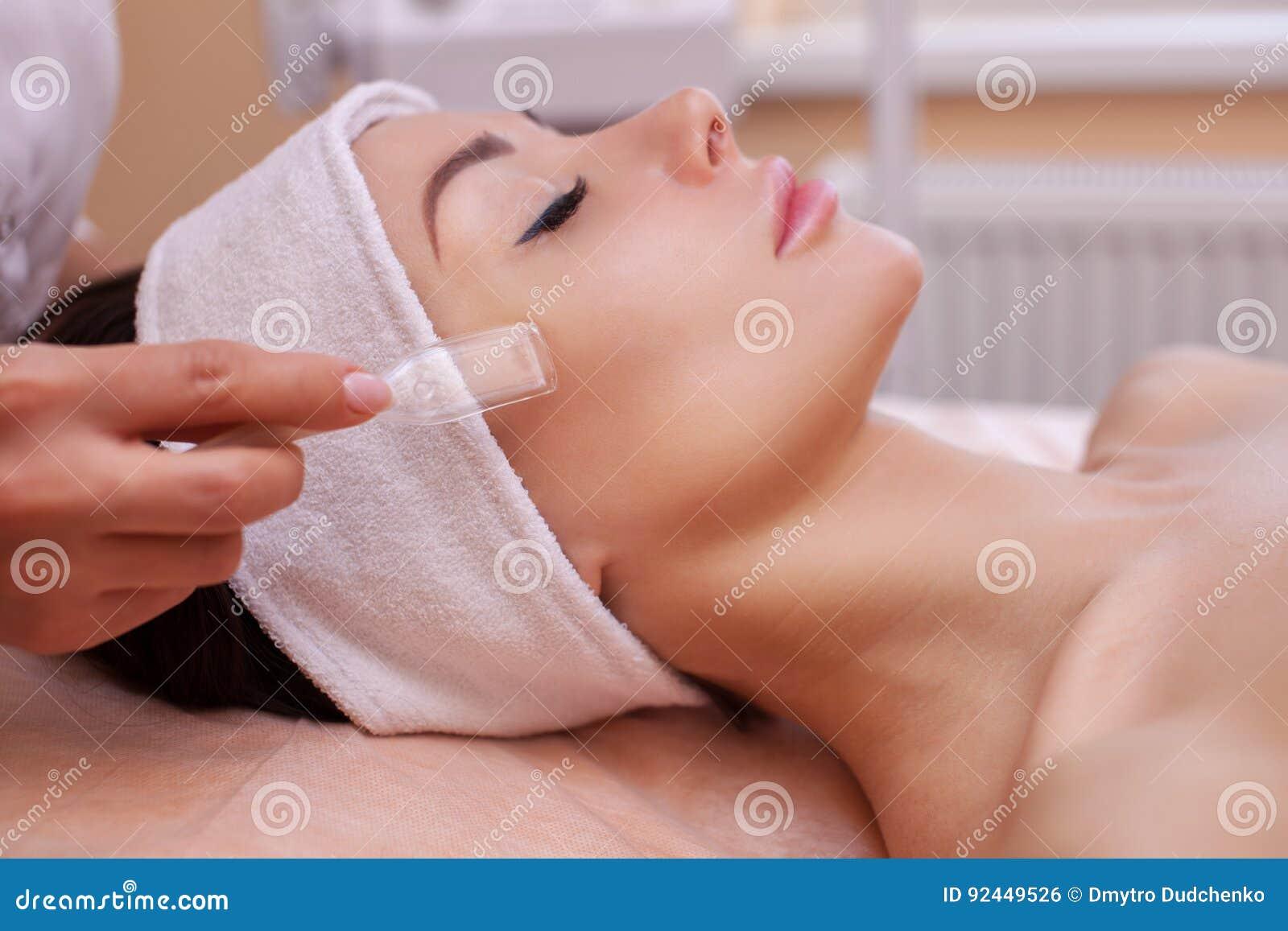 El doctor-cosmetologist hace la limpieza de la cara del vacío del procedimiento de una mujer hermosa, joven