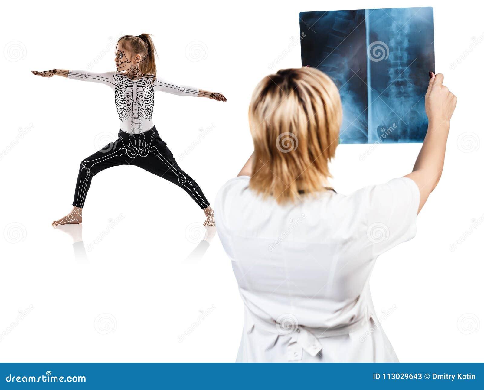 El doctor de sexo femenino mira en la radiografía de la niña en actitud de la yoga