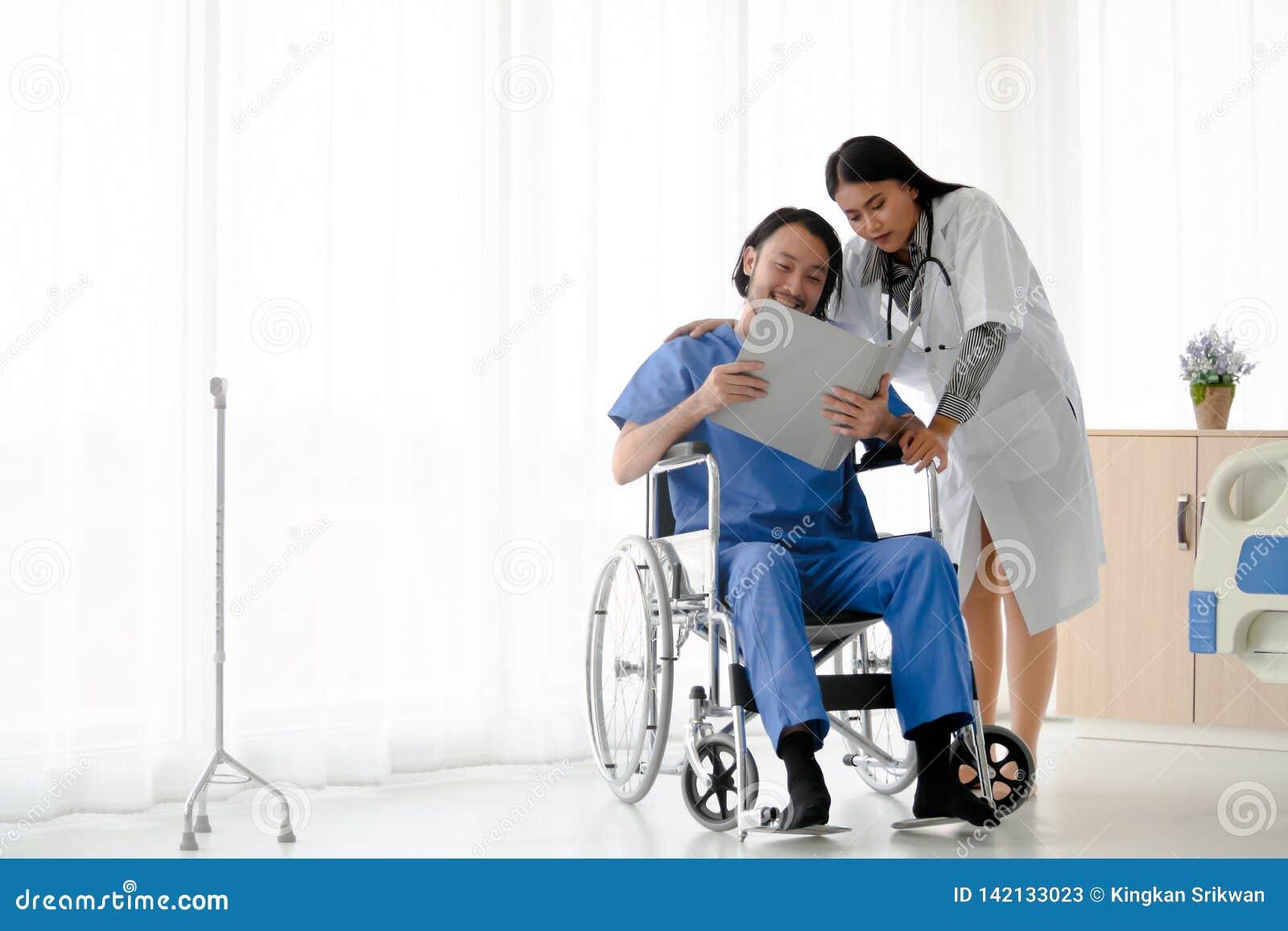 El doctor de sexo femenino toma el cuidado del paciente masculino que sentándose en la silla de ruedas