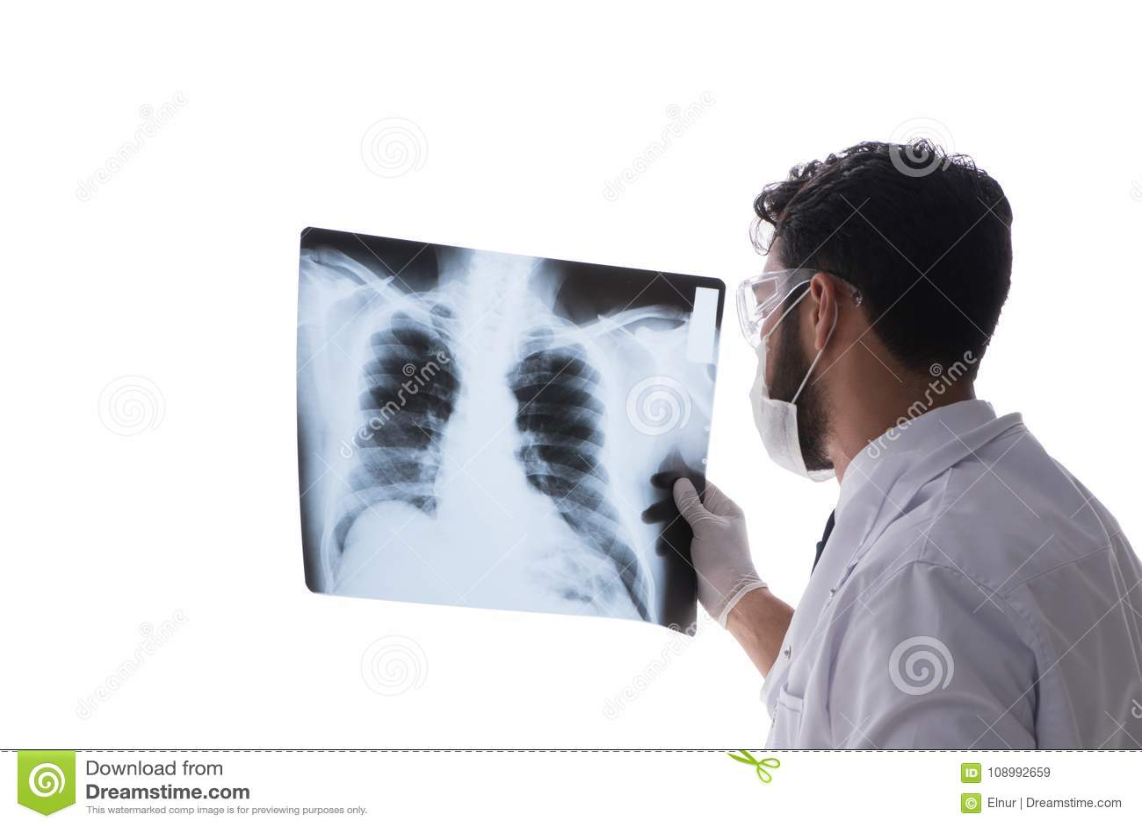 El doctor joven que mira las imágenes de la radiografía aisladas en blanco