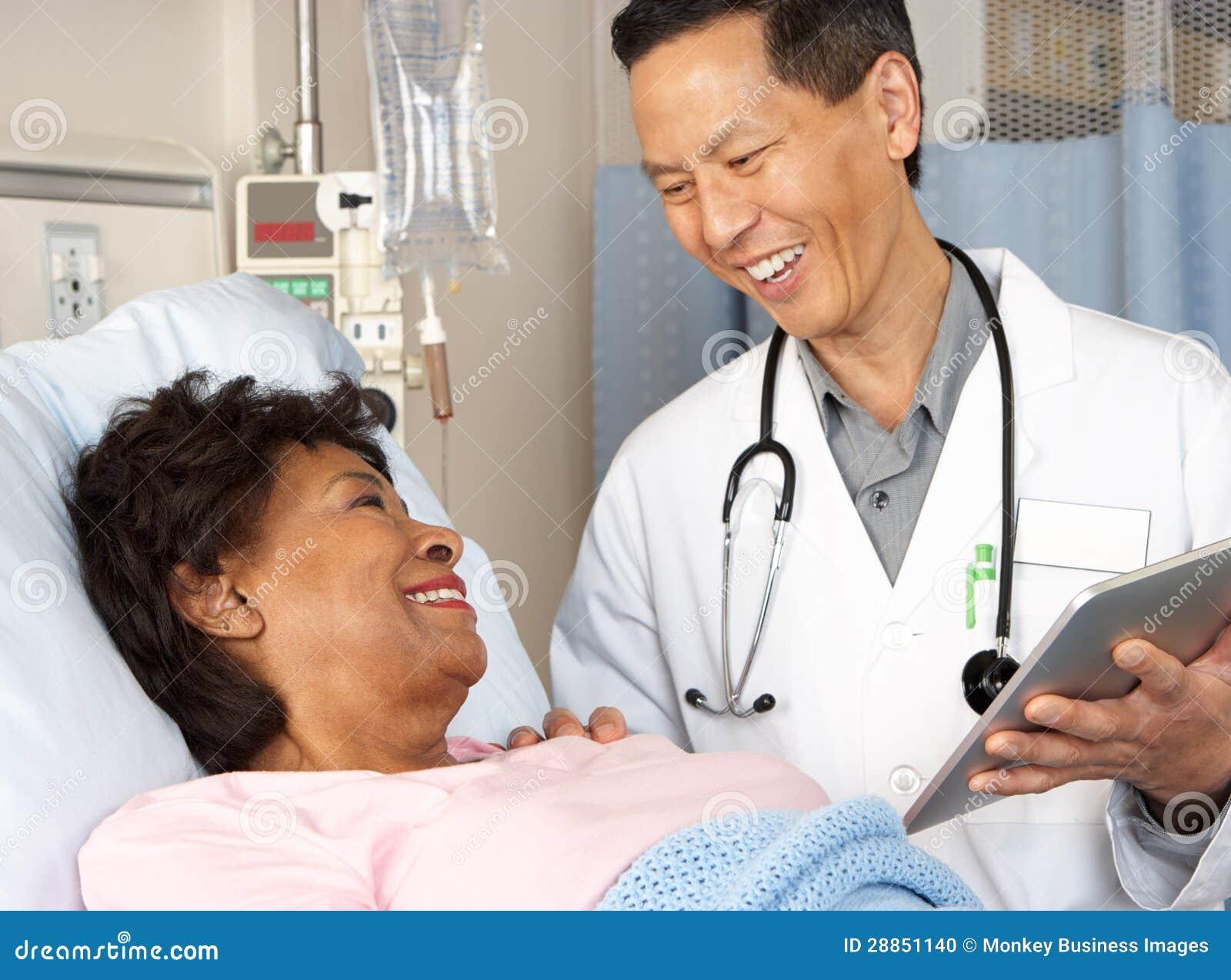 El doctor Using Digital Tablet Talking con el paciente mayor