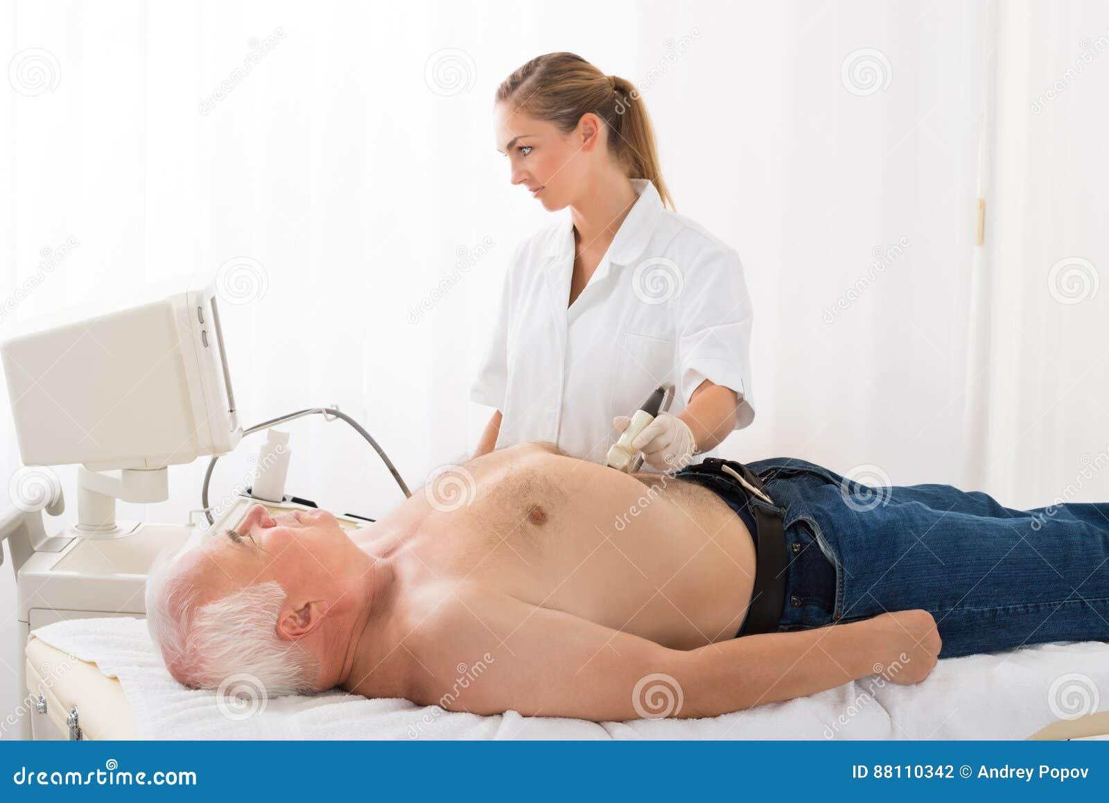 El doctor Using Ultrasound Scan en el abdomen del paciente masculino
