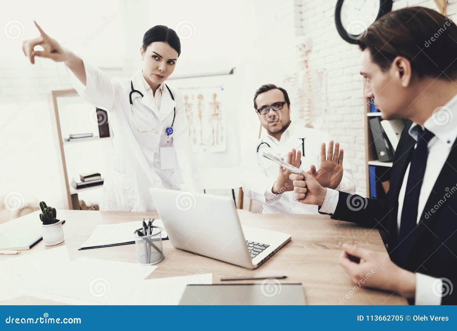 El doctor y la enfermera honestos rechaza tomar el soborno del paciente en oficina médica