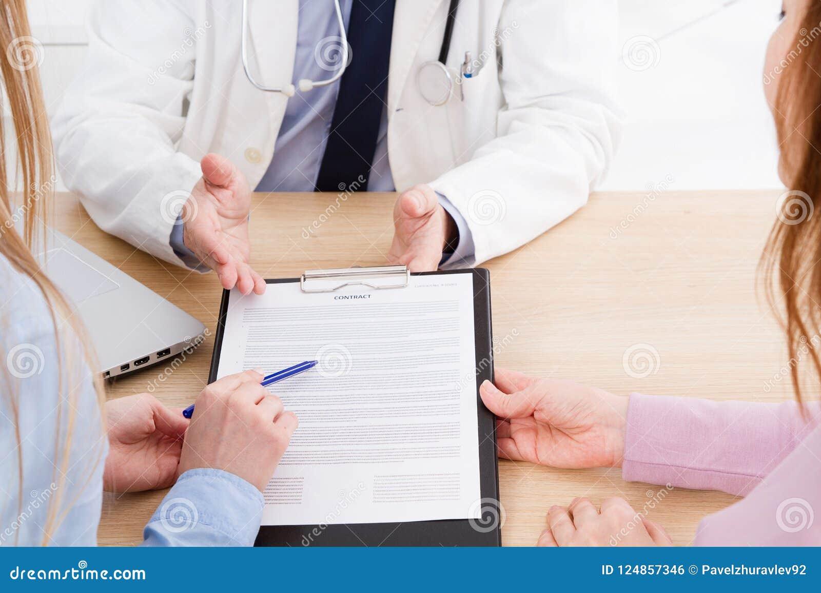 El doctor y el paciente están discutiendo algo, manos en la tabla Seguro médico Doc. que se sienta en gabinete Hombre en uniforme
