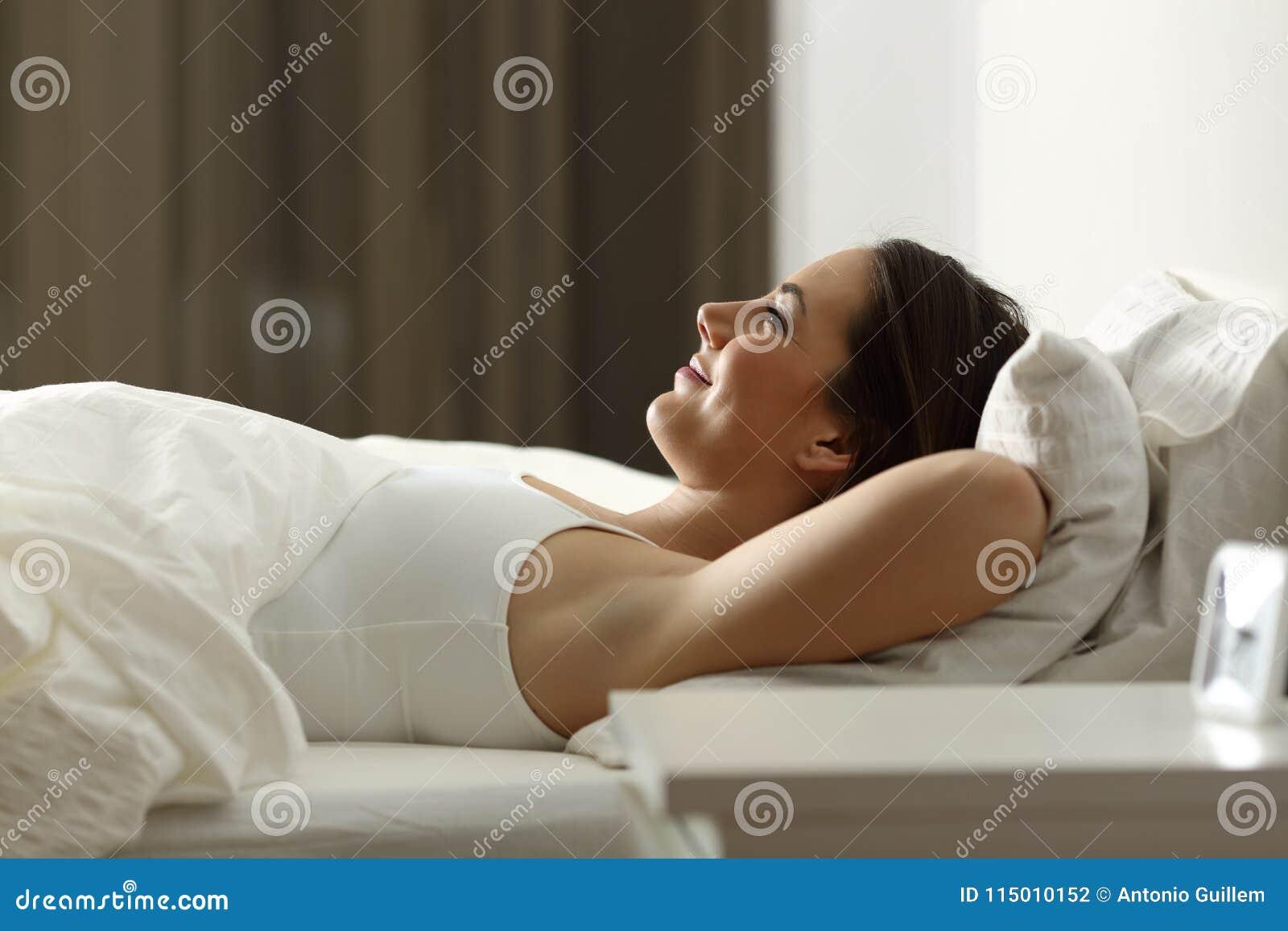 El dormir de relajación de la mujer en casa en la noche