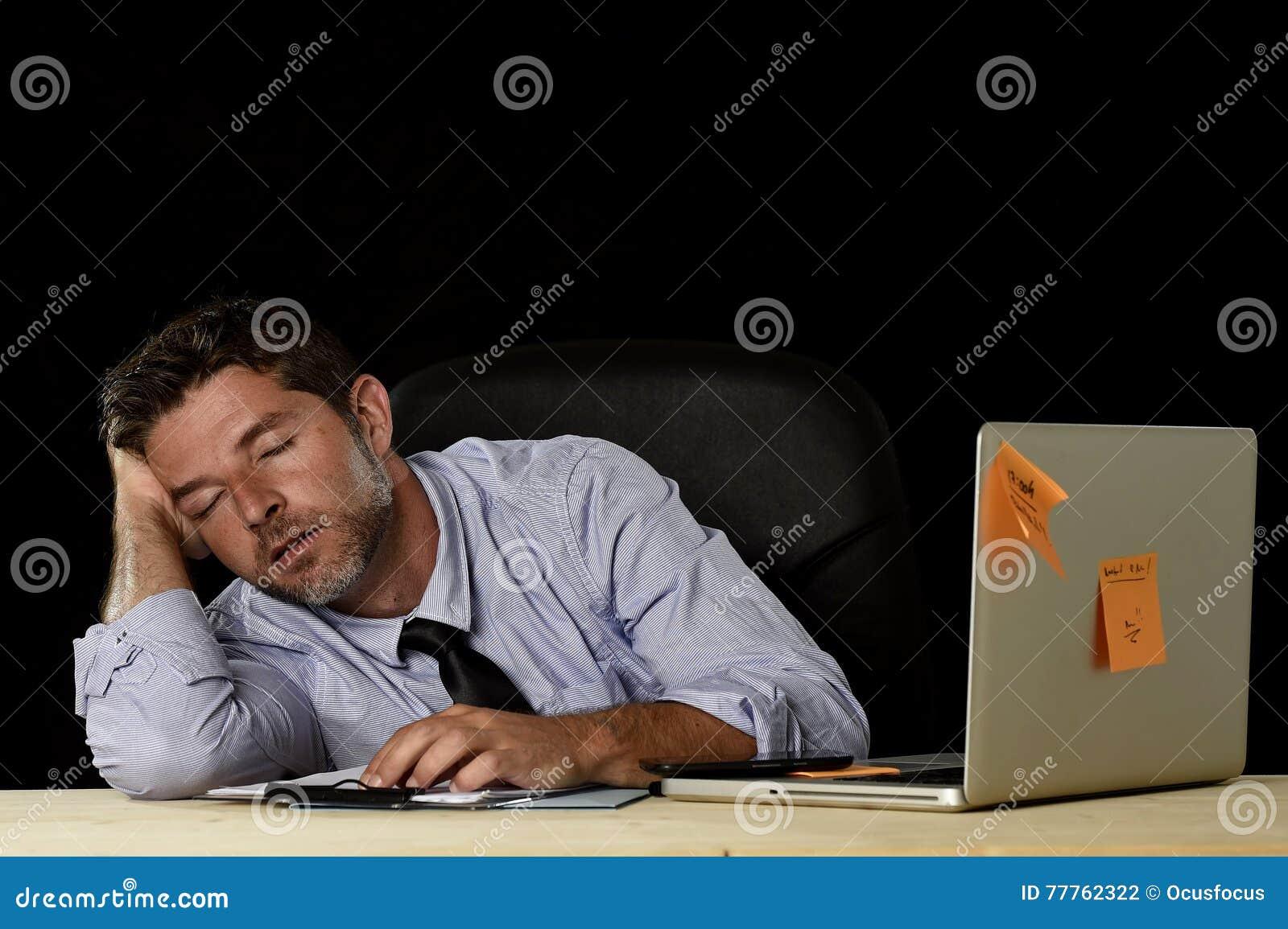 El dormir del hombre de negocios perdido cansado en el escritorio del ordenador de oficina en largases horas del trabajo