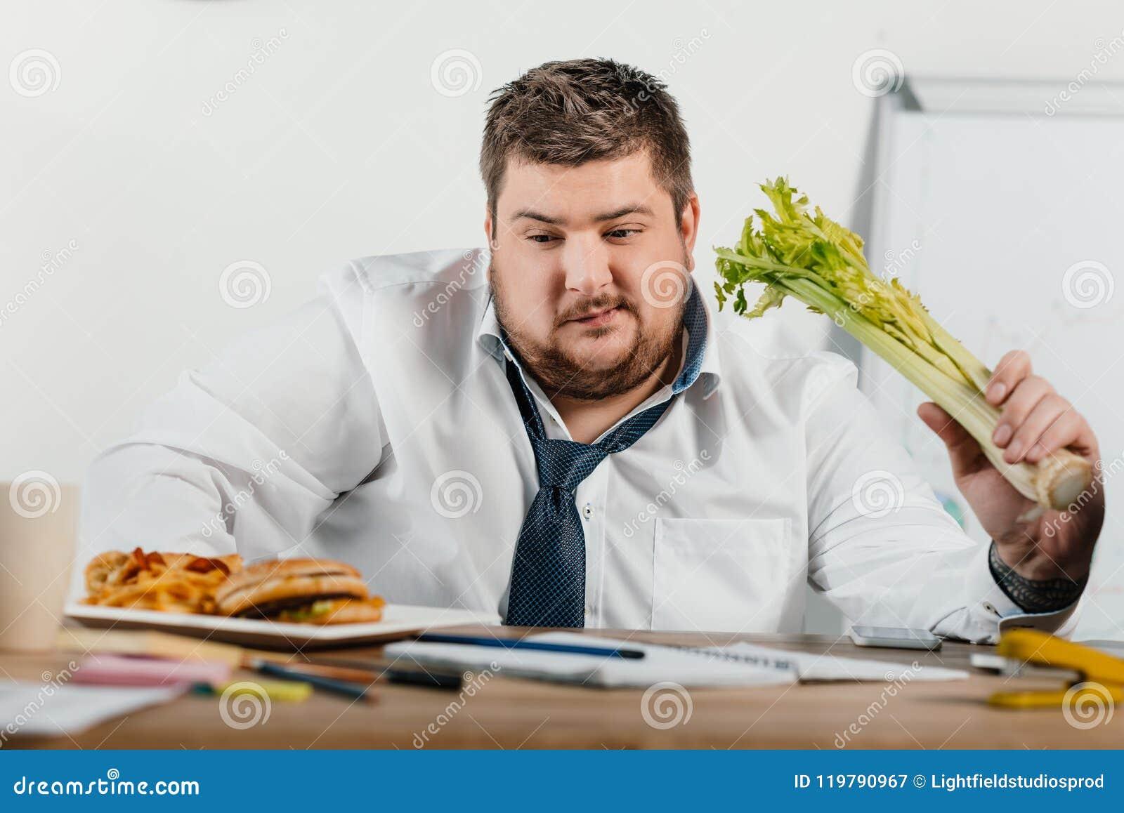 El elegir gordo pensativo del hombre de negocios sano o comida basura en el lugar de trabajo