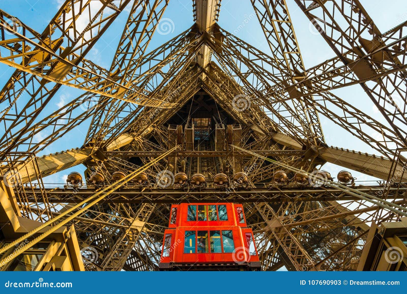 El elevador rojo trae a turistas abajo del eje en la estructura de la torre Eiffel del metal en París