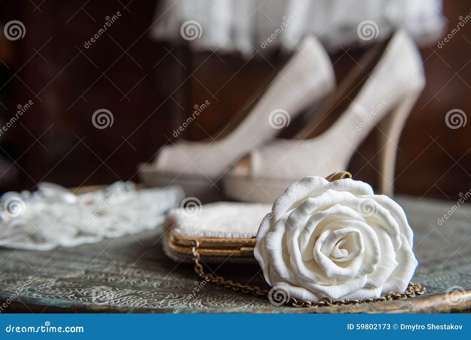 El embrague de las mujeres con la rosa, los zapatos y la liga del blanco en la bandeja de cobre amarillo con un ornamento