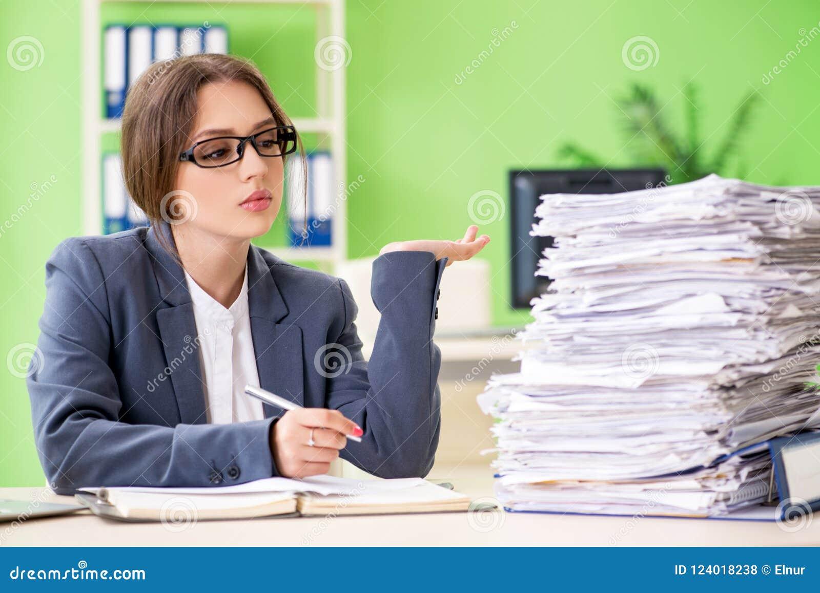 El empleado de sexo femenino joven muy ocupado con papeleo en curso