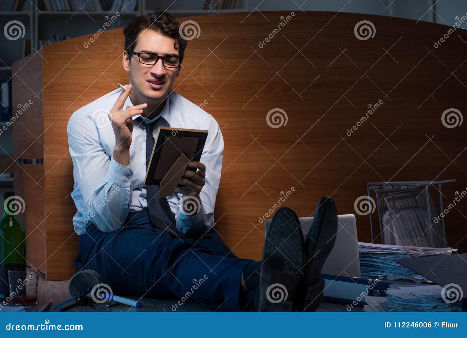 El empleado triste en la oficina que falta a su esposa después de la separación del divorcio