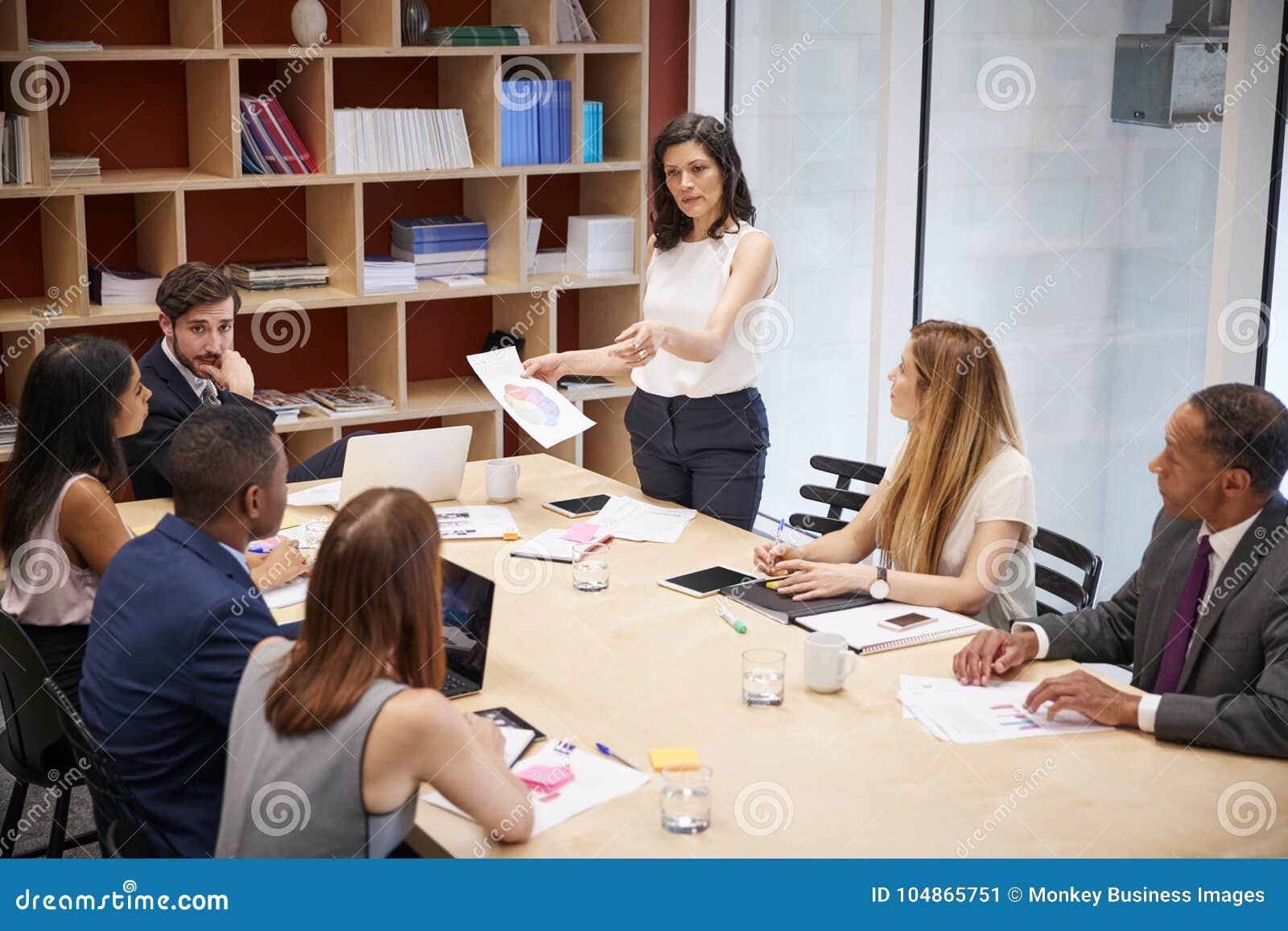 El encargado de sexo femenino se coloca con el documento en la reunión de la sala de reunión