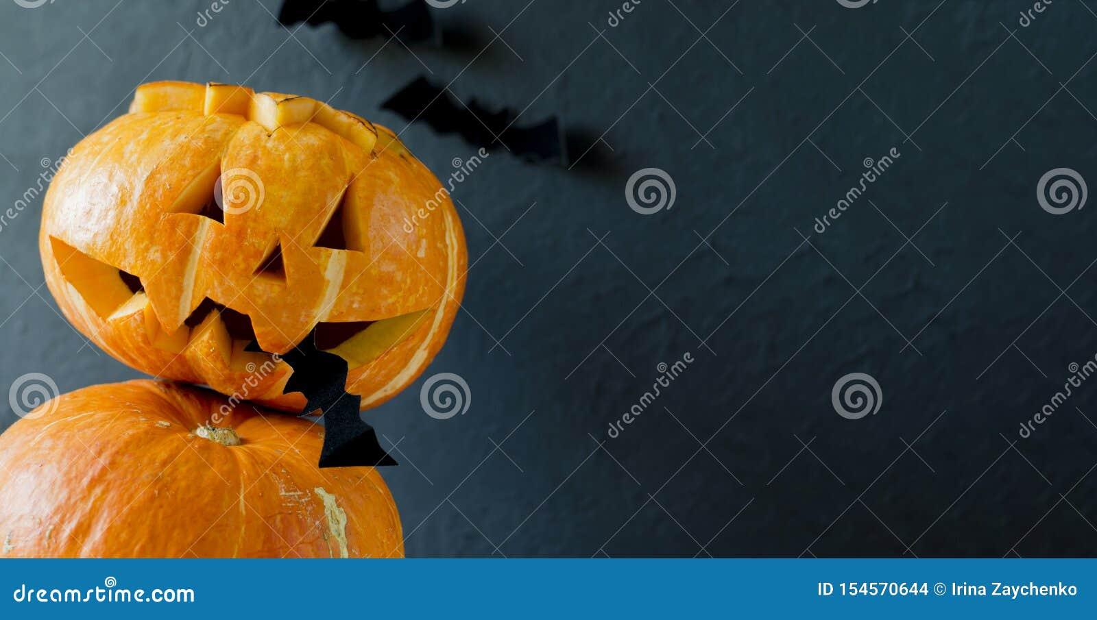 El enchufe de la linterna de la calabaza del primer de Halloween en su boca sostiene un palo Fondo oscuro Dos calabazas Tres palo