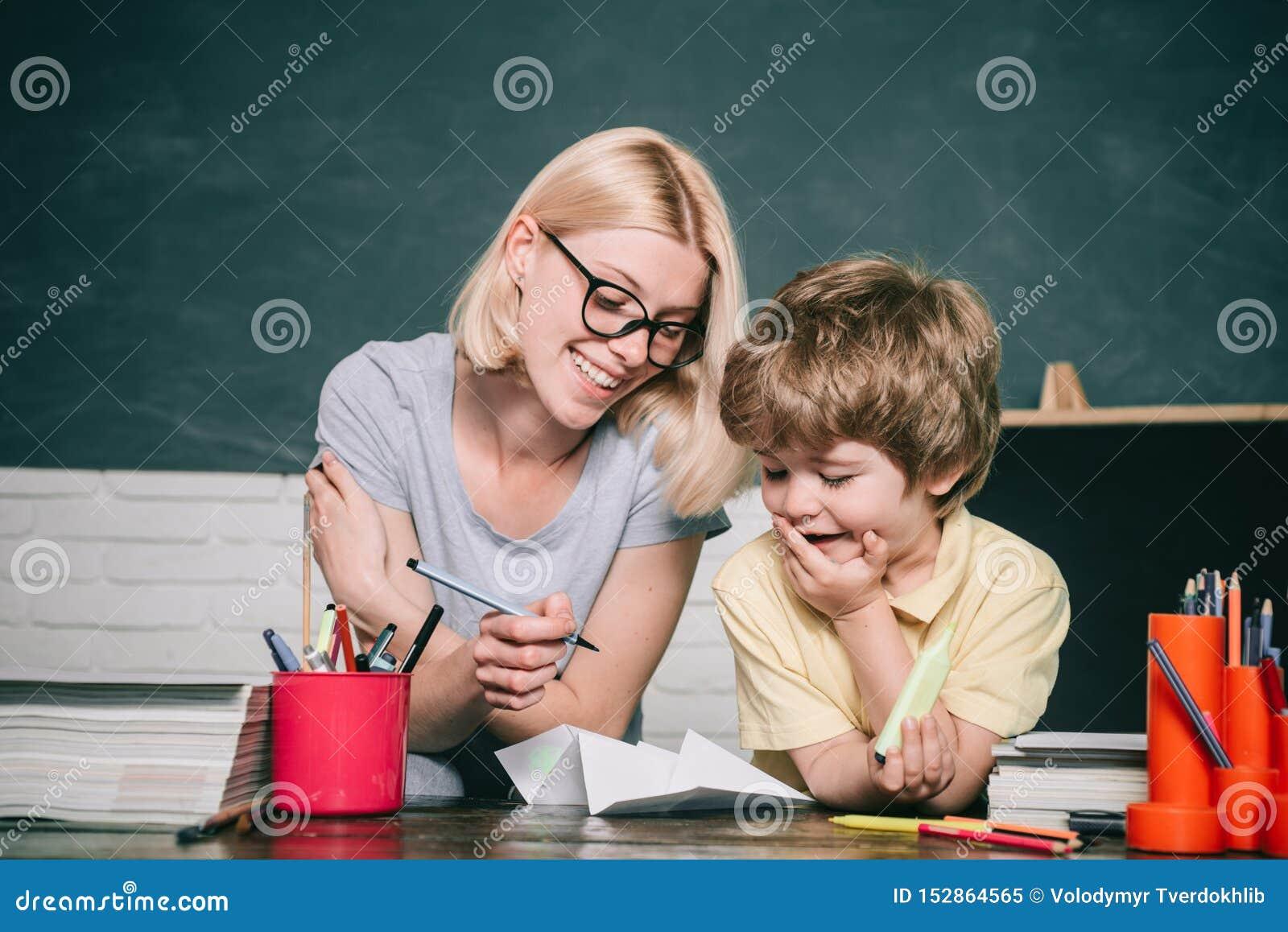 El enseñar casero o escuela privada Ni?os de ayuda del profesor con su preparaci?n en sala de clase en la escuela Alumnos