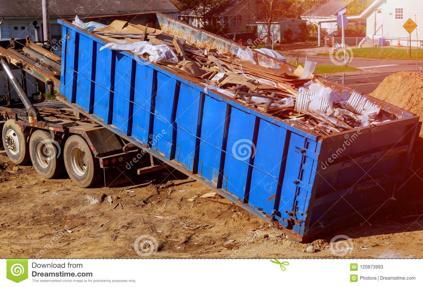 El envase azul de la ruina de construcción llenó de la roca y de escombros concretos Compartimiento de basura industrial