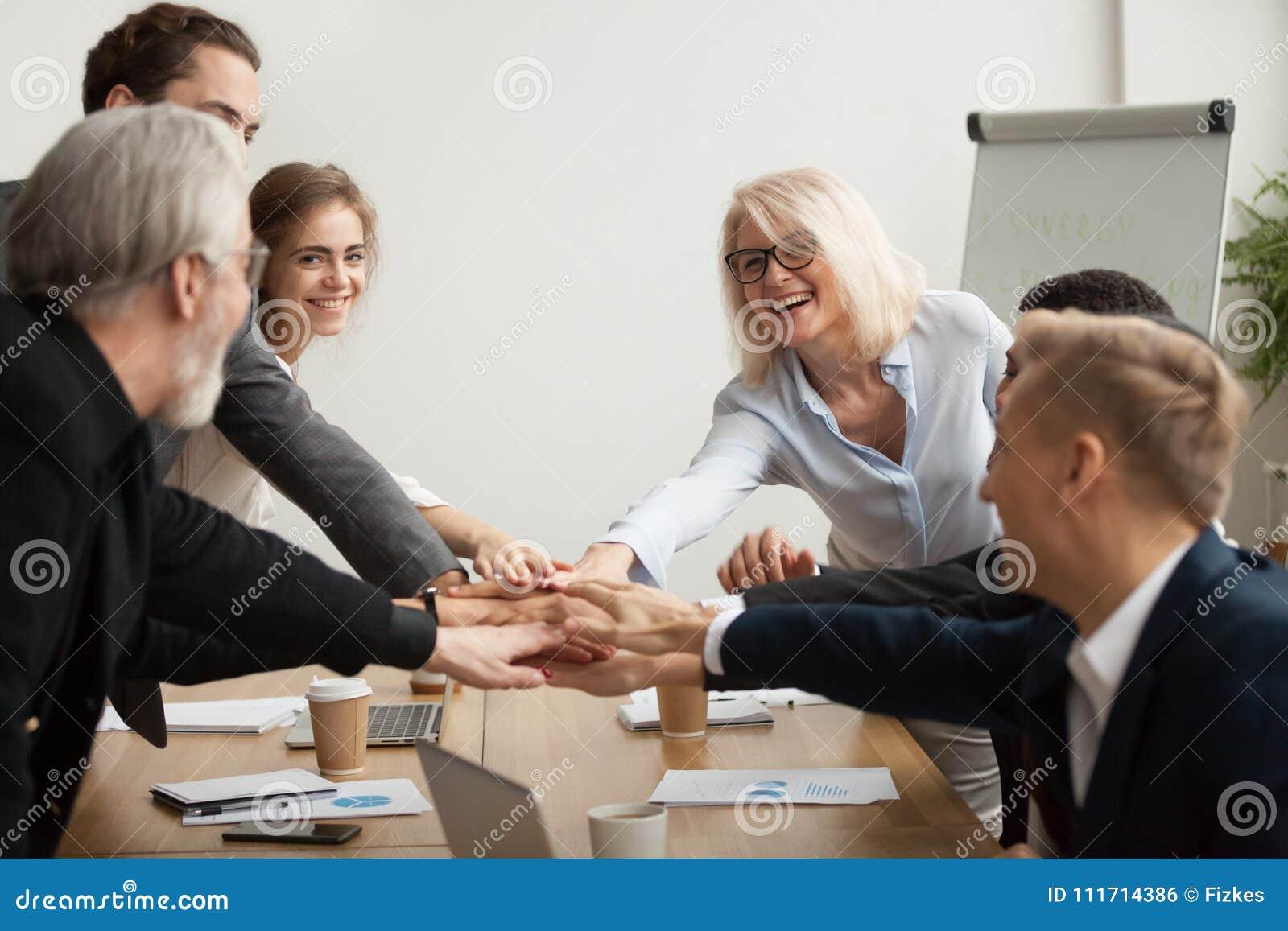 El equipo corporativo sonriente feliz se une a las manos juntas en el meetin del grupo