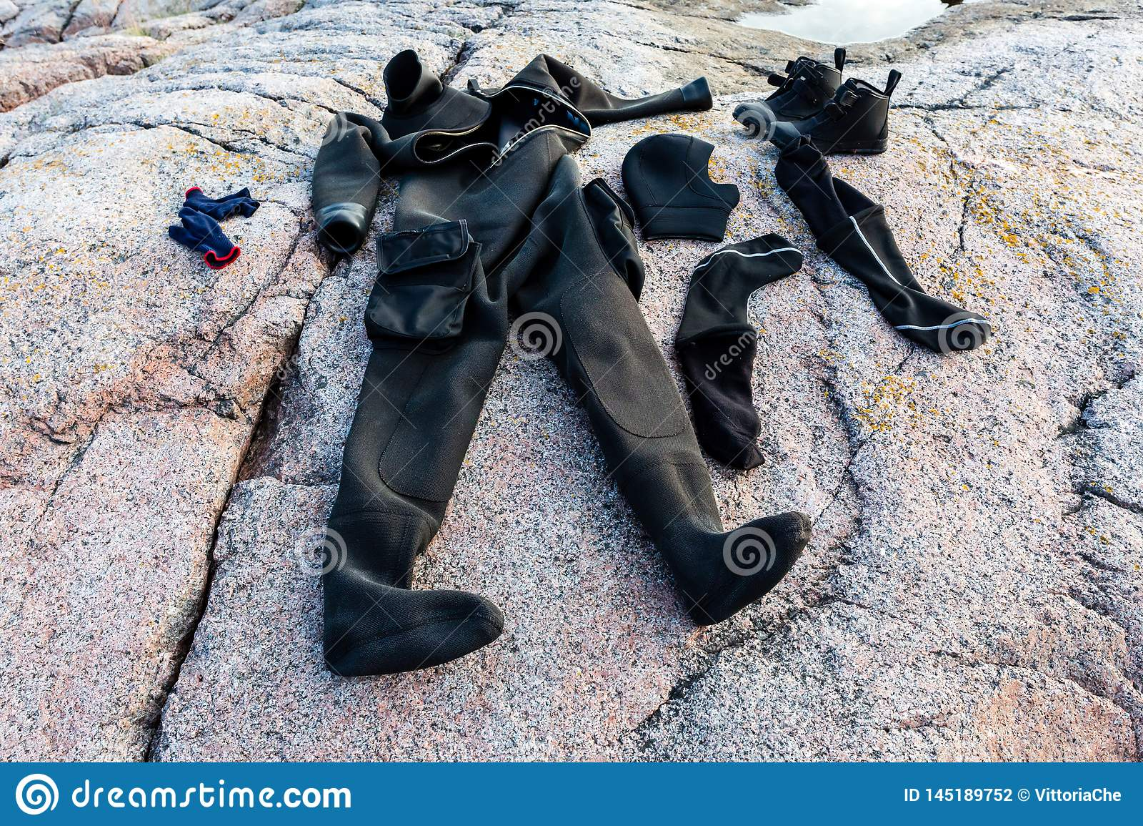 El equipo de buceo se seca despu?s de zambullirse en la costa de piedra