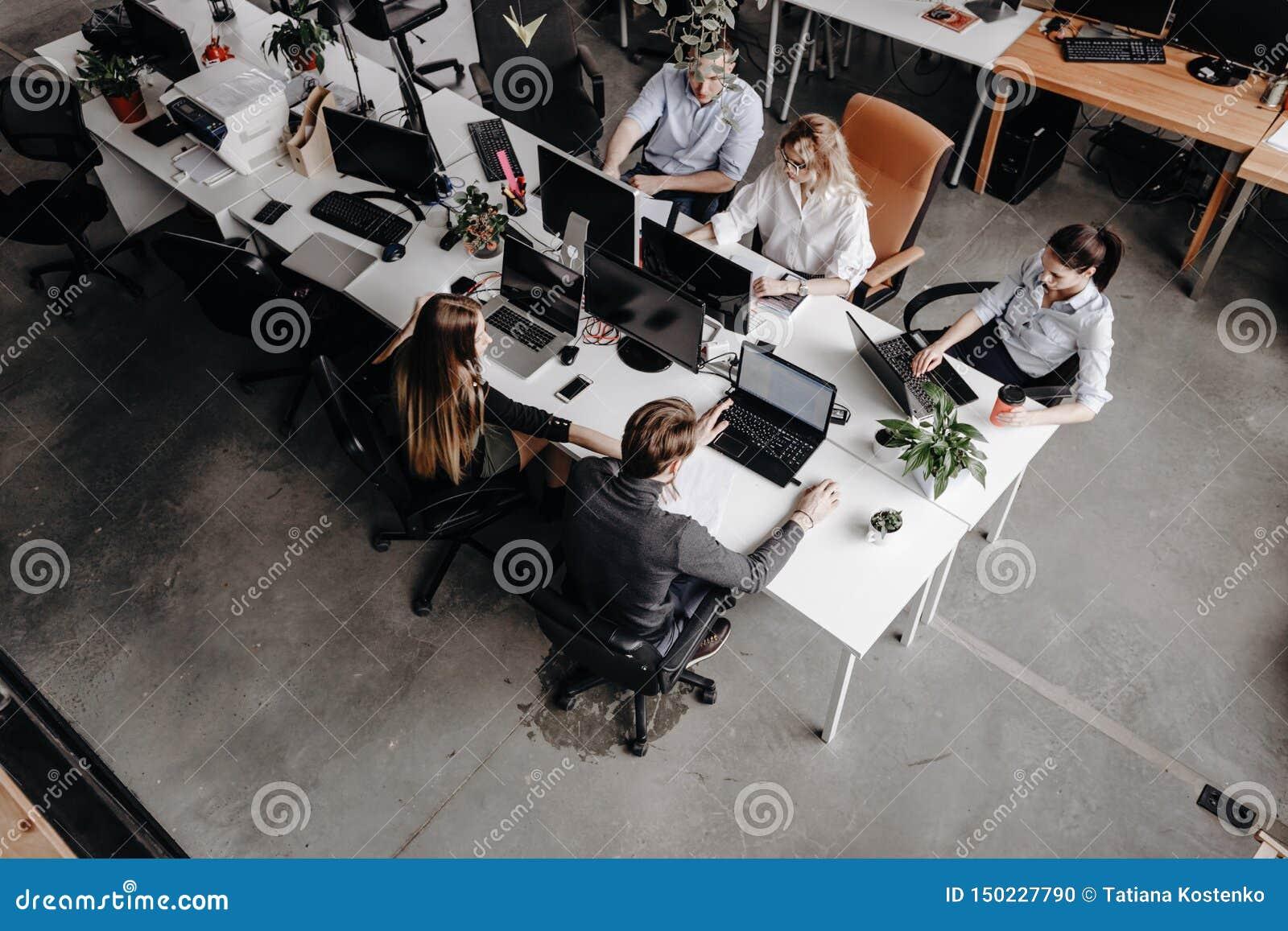 El equipo de colegas trabaja con el ordenador portátil y los documentos que se sientan en los escritorios en una oficina moderna