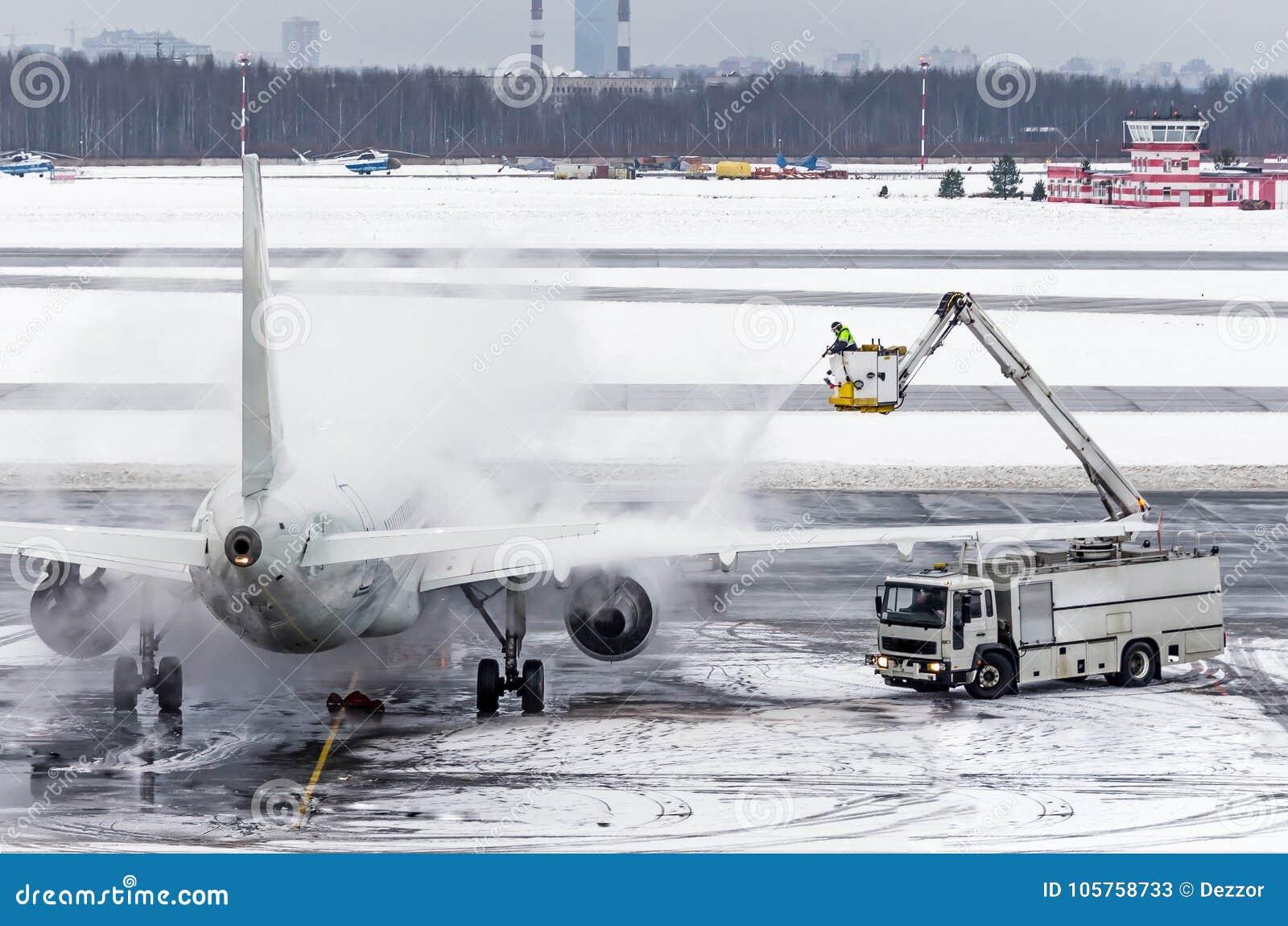 El equipo de tierra proporciona a de icing Están pintando (con vaporizador) el avión, que previene el acontecimiento de la helada