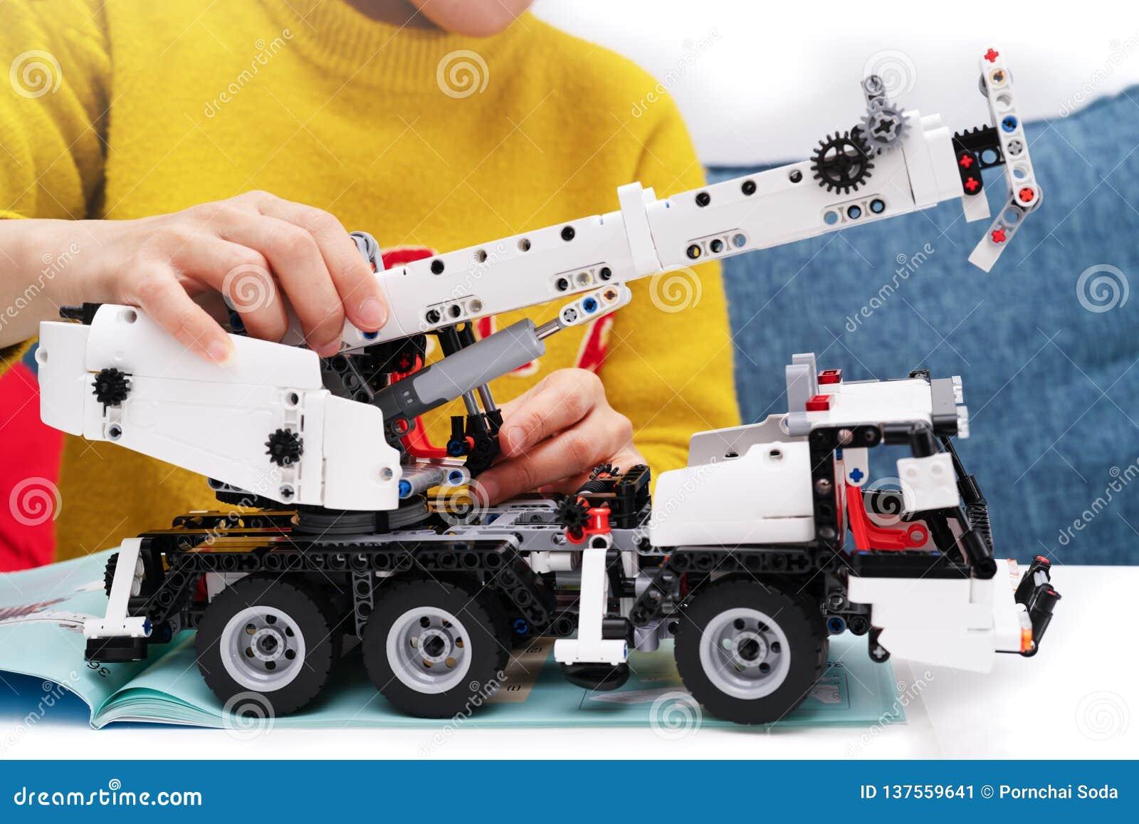 El equipo del montaje del coche, mujer monta un juguete muy complicado y común del coche camión