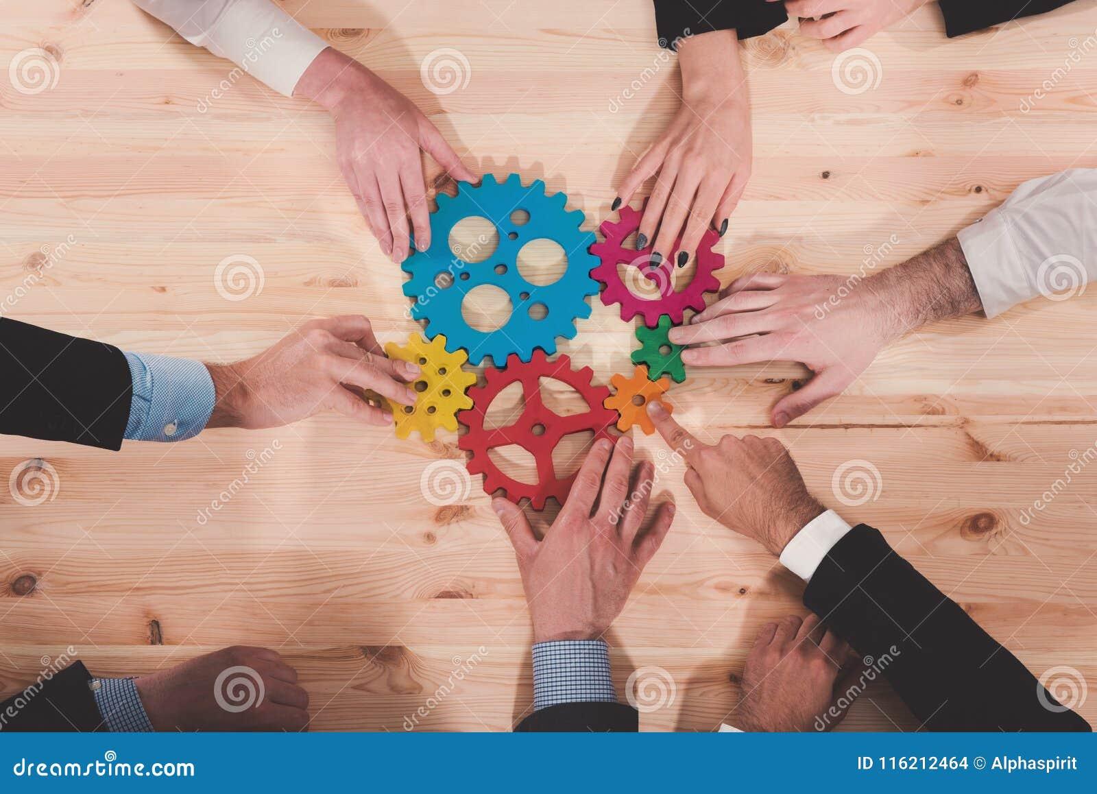 El equipo del negocio conecta pedazos de engranajes Trabajo en equipo, sociedad y concepto de la integración