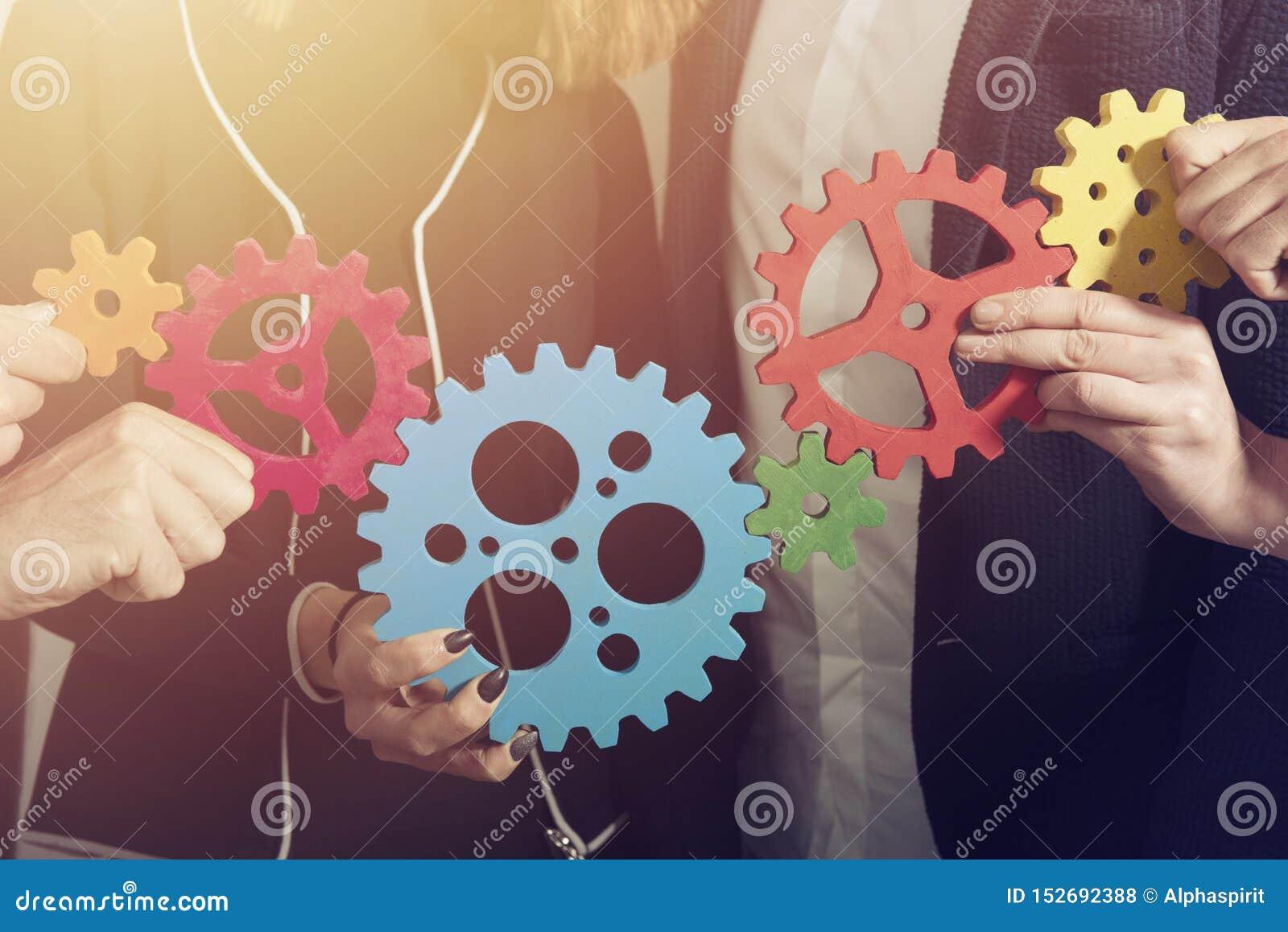 El equipo del negocio conecta pedazos de engranajes Trabajo en equipo, sociedad y concepto de la integraci?n
