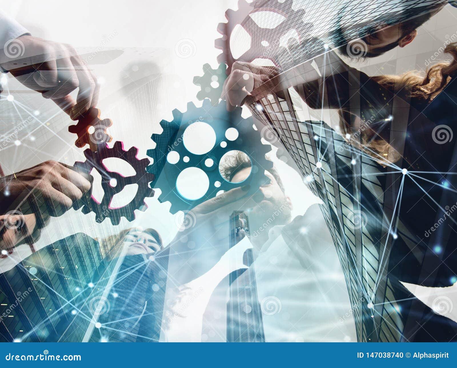 El equipo del negocio conecta pedazos de engranajes Trabajo en equipo, sociedad y concepto de la integraci?n exposici?n doble con