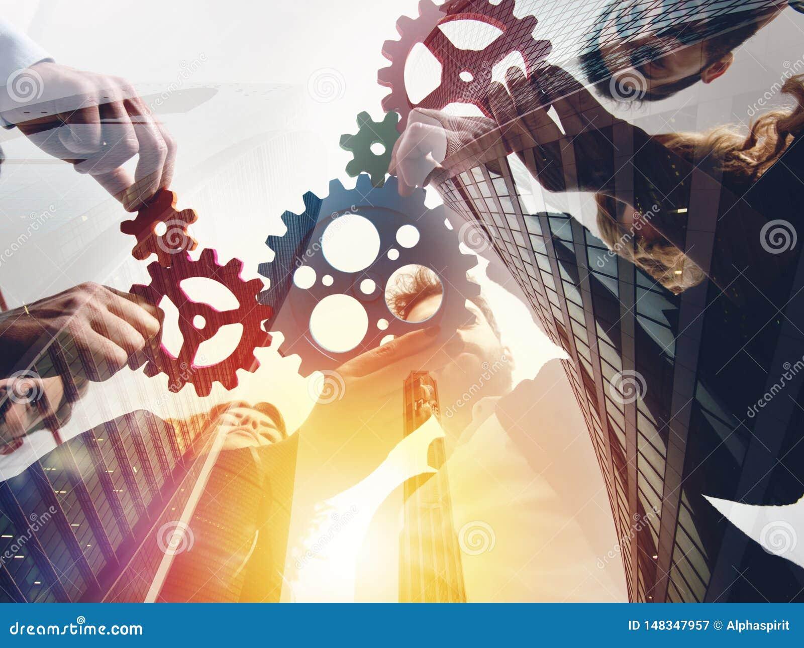 El equipo del negocio conecta pedazos de engranajes Trabajo en equipo, sociedad y concepto de la integraci?n Exposici?n doble