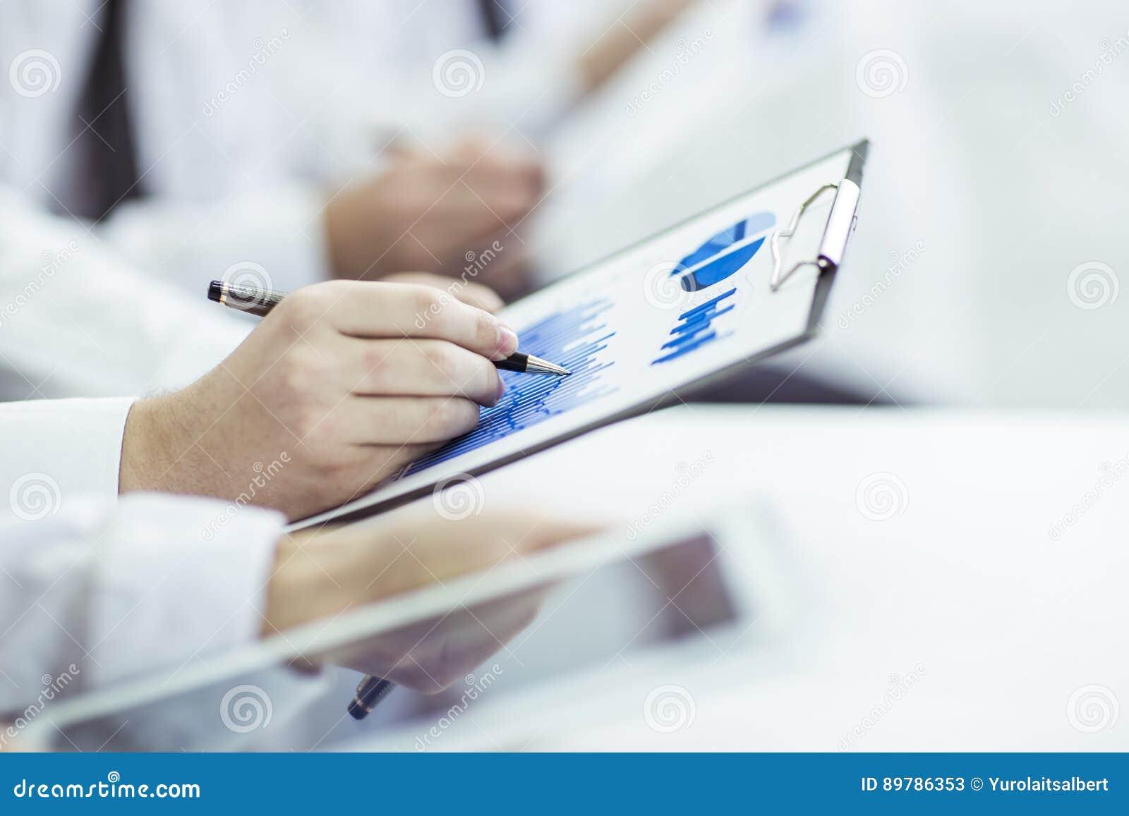 El equipo del negocio usando la tableta digital realiza el análisis de los gráficos del márketing