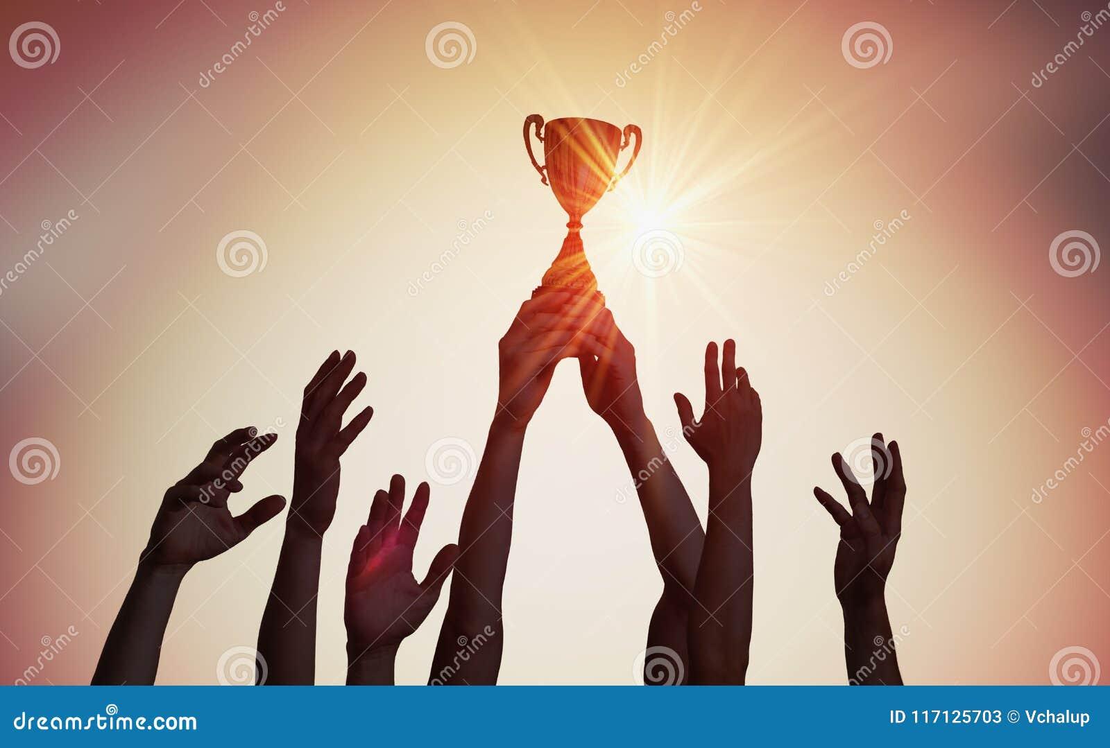 El equipo que gana está sosteniendo el trofeo en manos Siluetas de muchas manos en puesta del sol