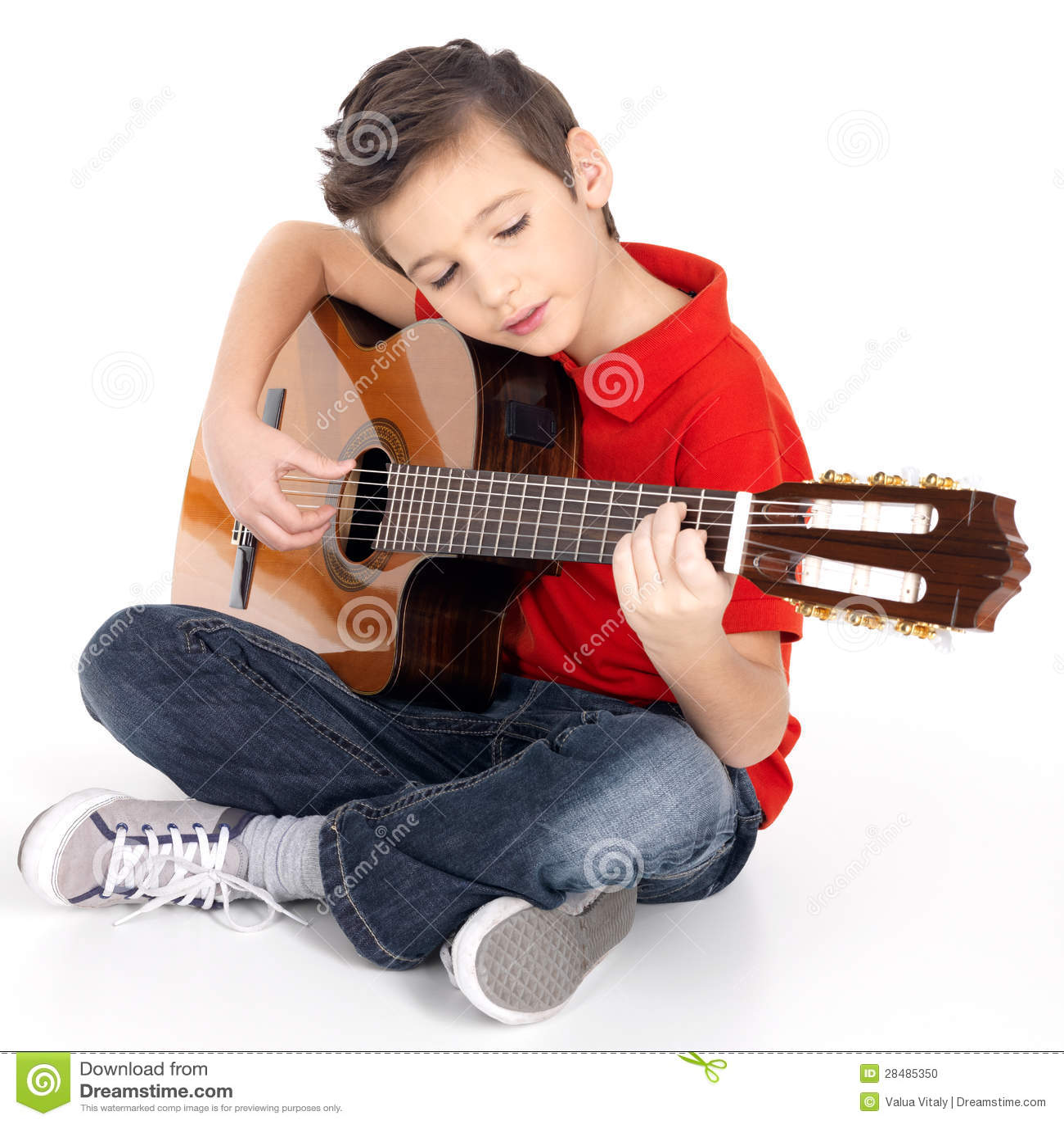El escolar está tocando la guitarra acústica