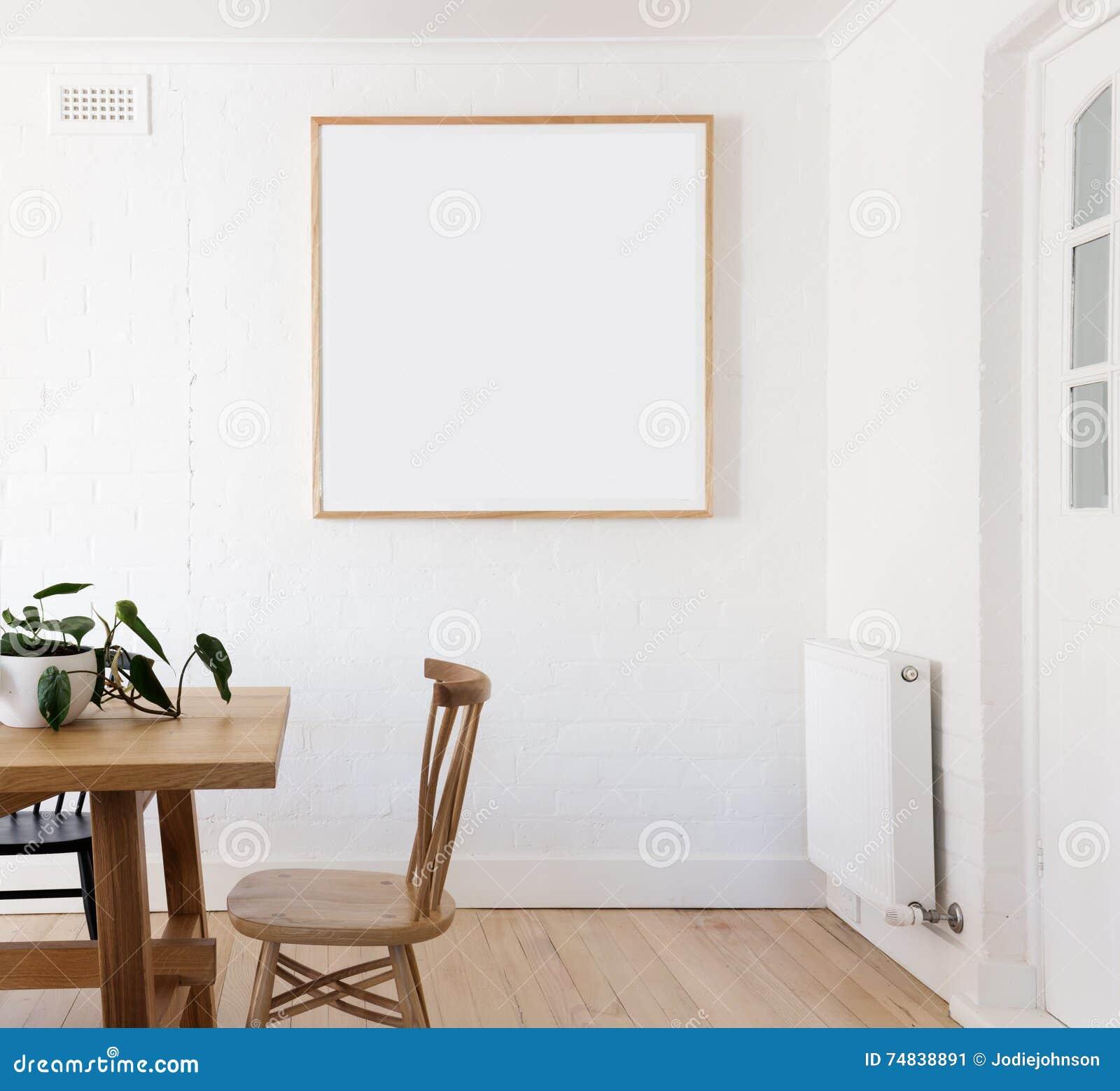 El espacio en blanco enmarcó la impresión en la pared blanca en dinin interior diseñado danés