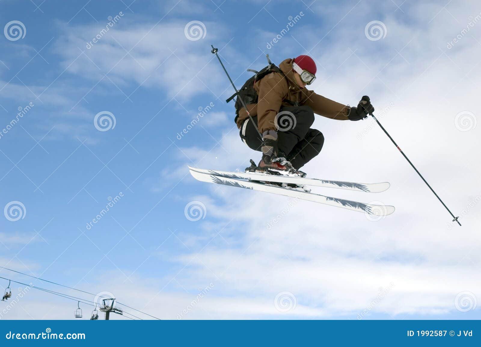 El esquiador que salta arriba en el aire