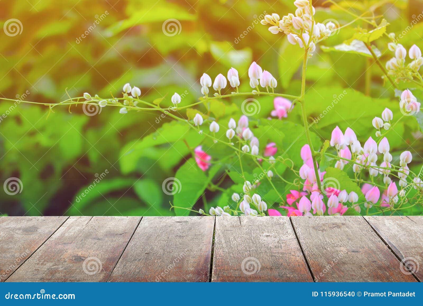 El estante de madera vacío del piso del tablero de la textura con la flor en fondo de la naturaleza con el espacio de la copia añ