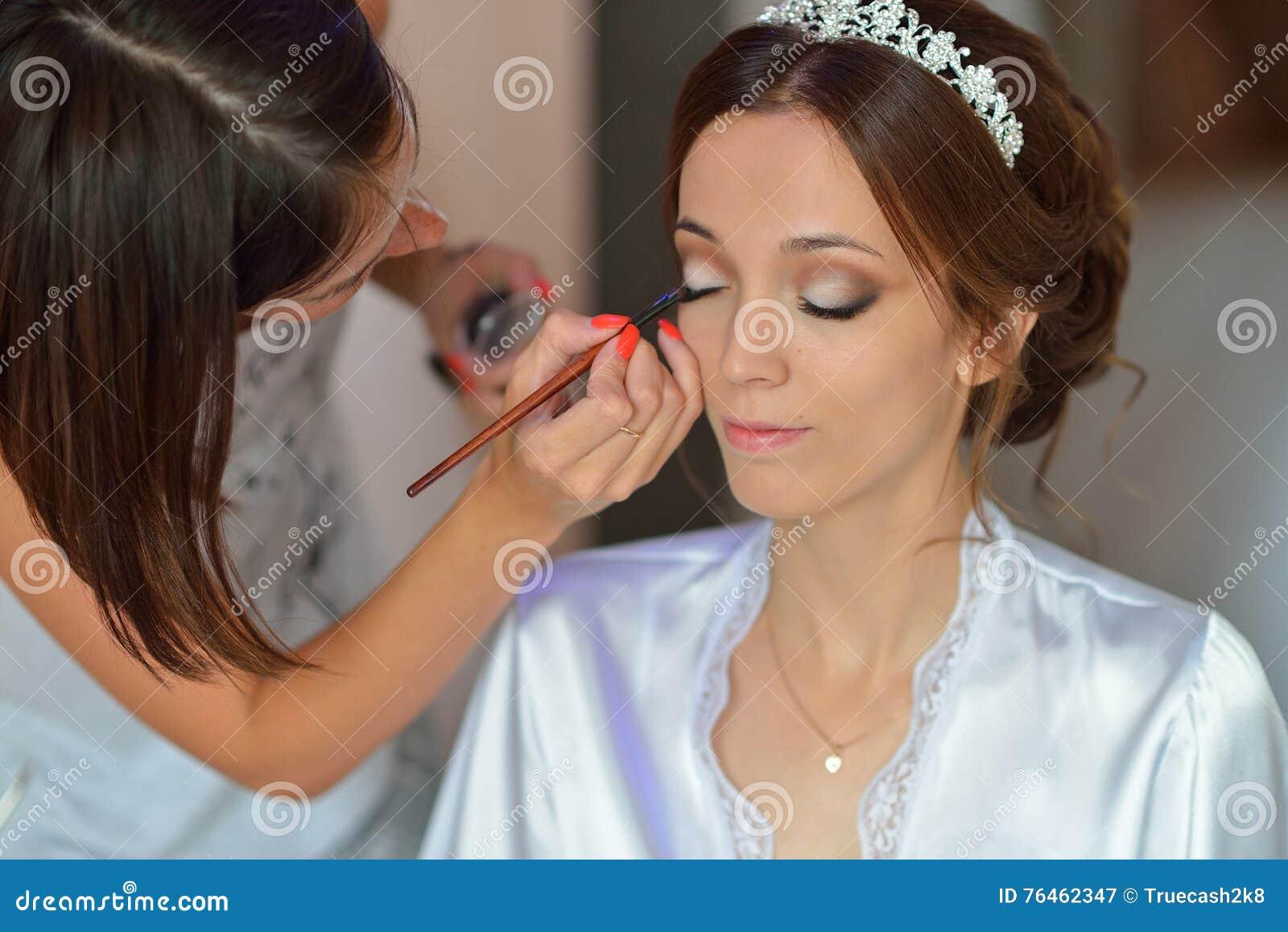 El estilista hace a la novia del maquillaje en el día de boda