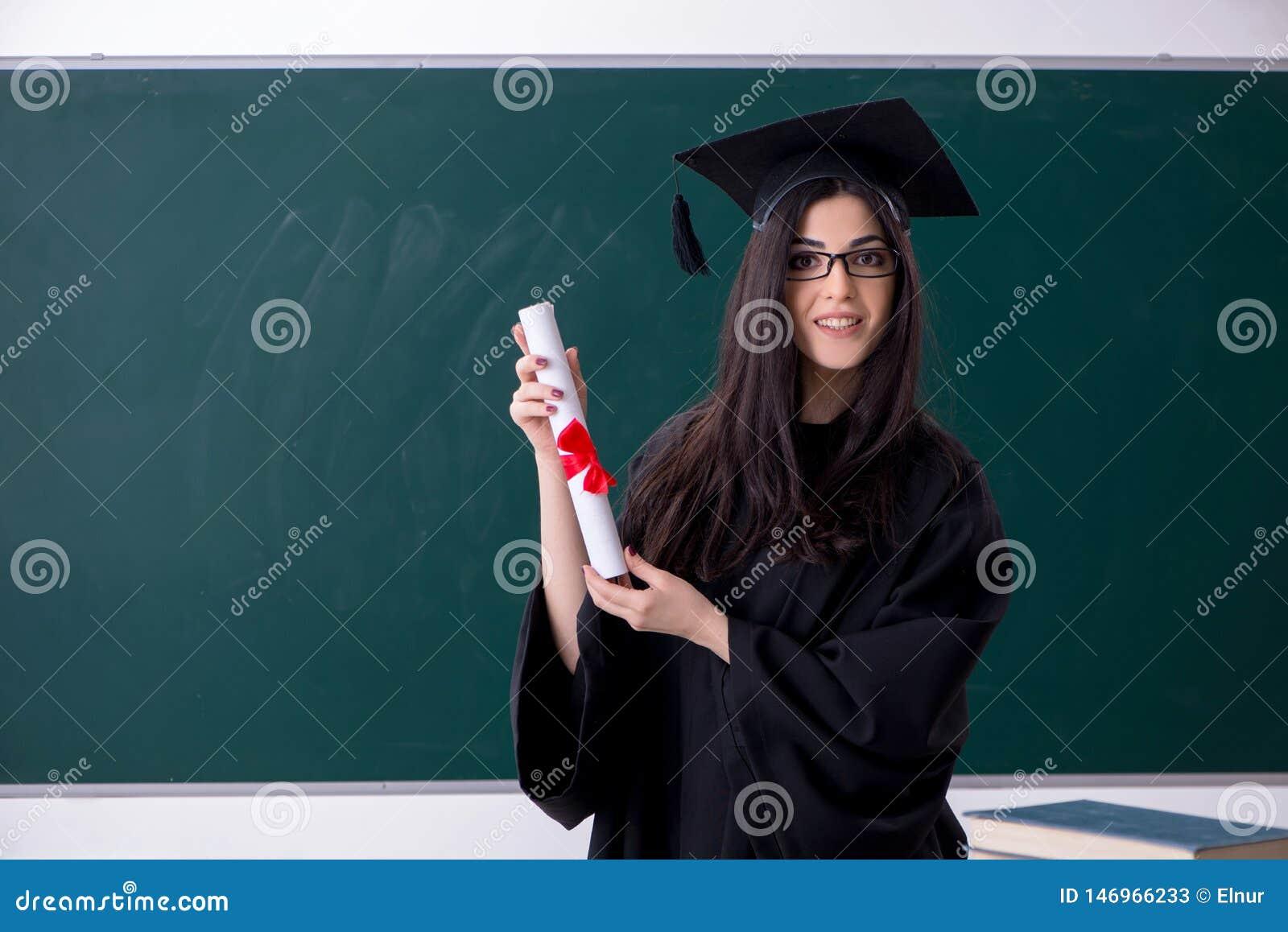 El estudiante de tercer ciclo de sexo femenino delante del tablero verde