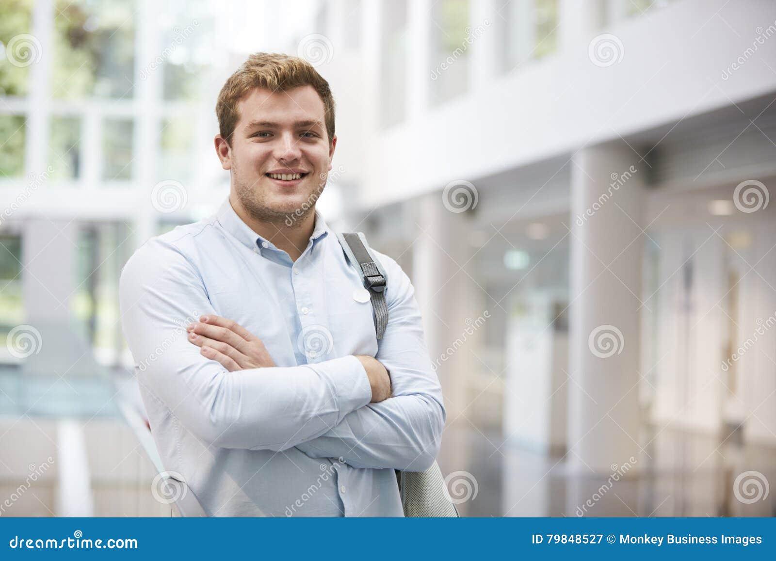 El estudiante masculino adulto sonriente en universidad moderna cabildea