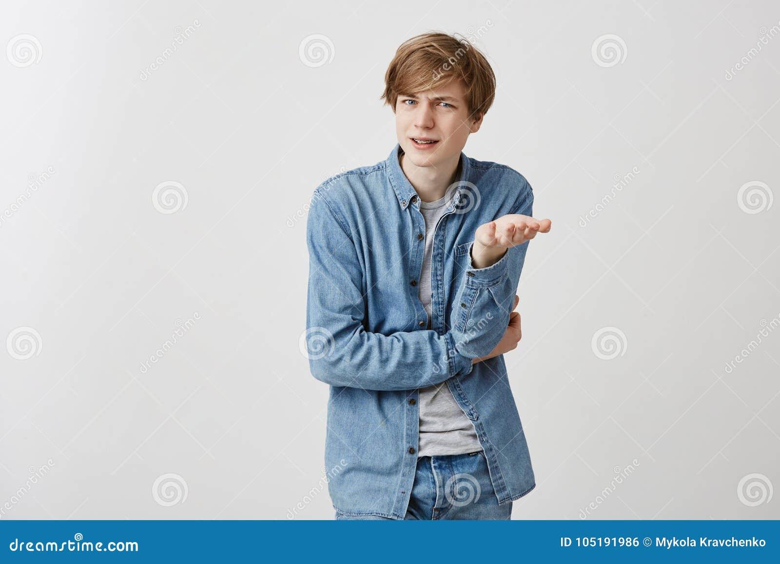 El estudiante masculino joven de pelo rubio enojado confuso gesticula en el desconcierto, expresa emociones negativas como tiene