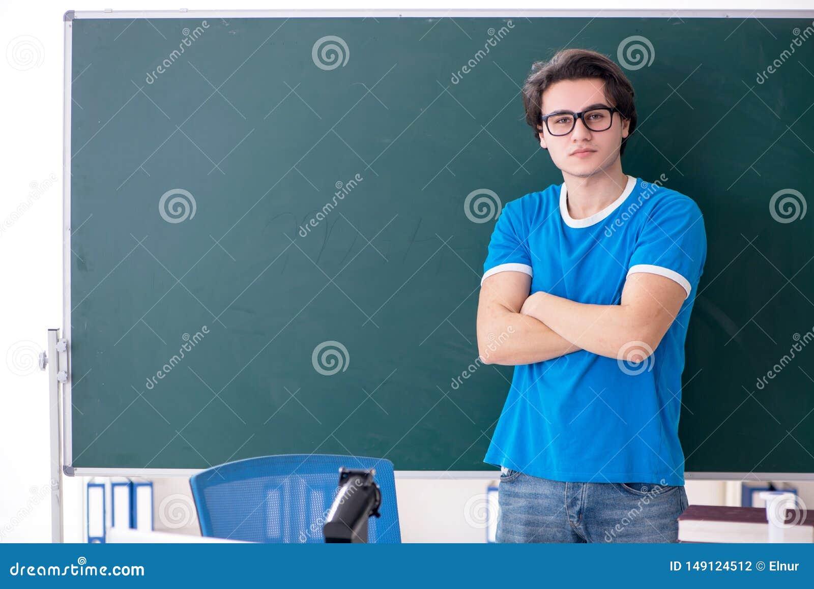 El estudiante masculino joven en la sala de clase